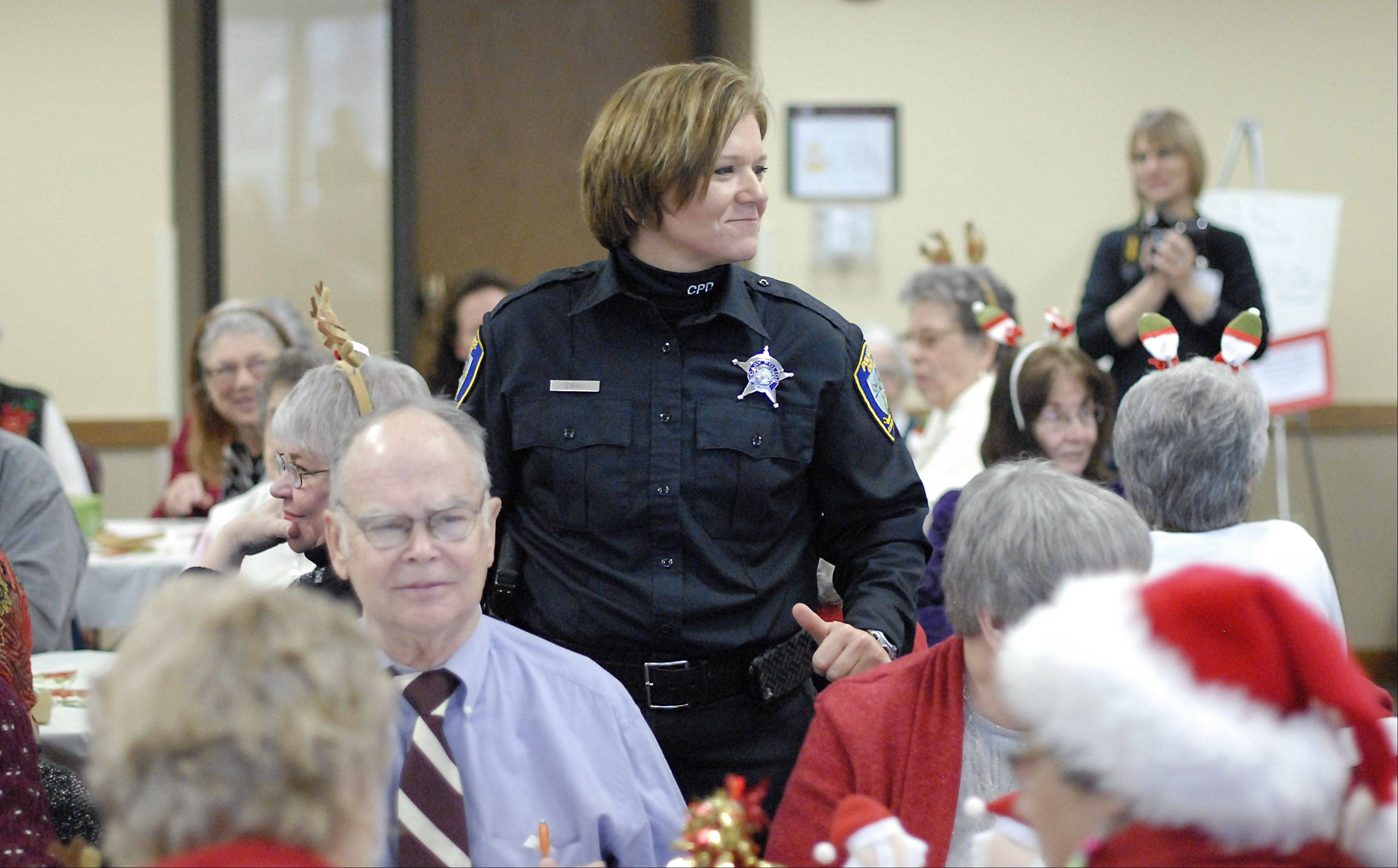 Cary police officer Kathy Eiring makes her rounds socializing with seniors during the Kraus Senior Center's Christmas party at the Community Center in Cary on Dec. 14. Eiring has been working with the senior community for eight years and was certified as an ESO four years ago.