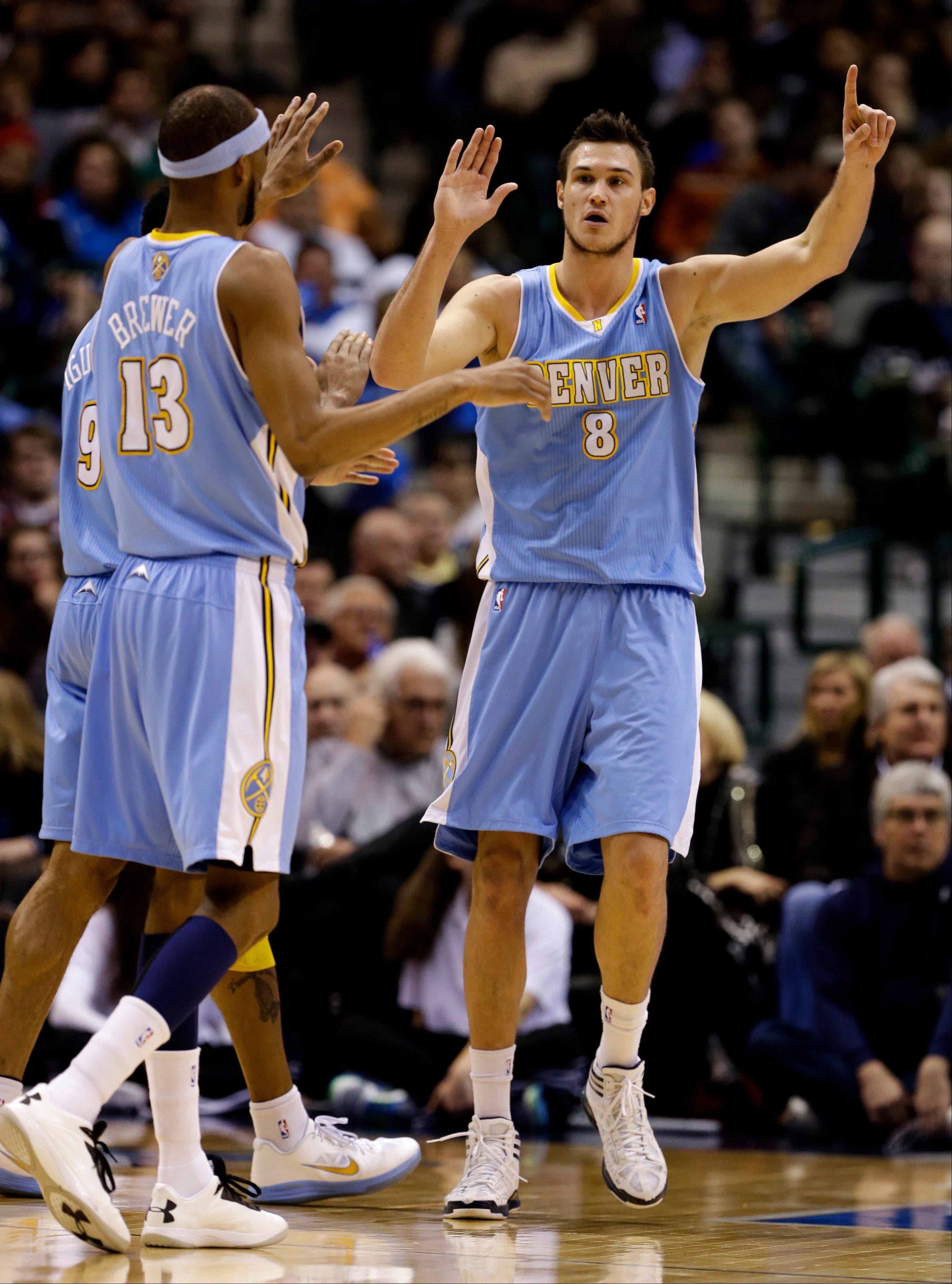 Denver�s Corey Brewer (13) and Andre Iguodala celebrate with teammate Danilo Gallinari after Gallinari scored in the second half Friday against the Dallas Mavericks in Dallas. Gallinari had a game-high 39-points in the 106-85 win.