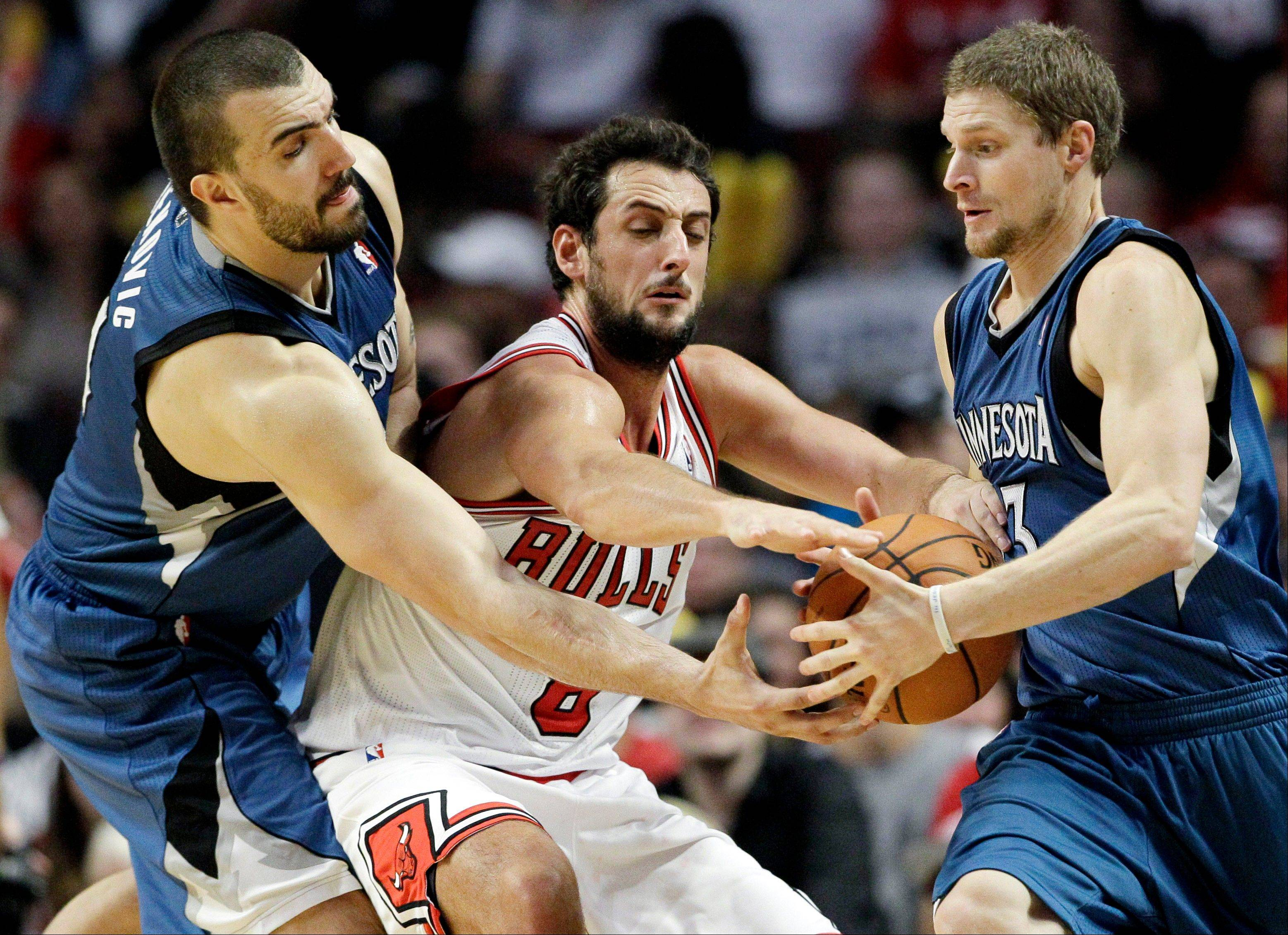 Minnesota Timberwolves center Nikola Pekovic, left, passes the ball to guard Luke Ridnour as Bulls guard Marco Belinelli, center, reaches.