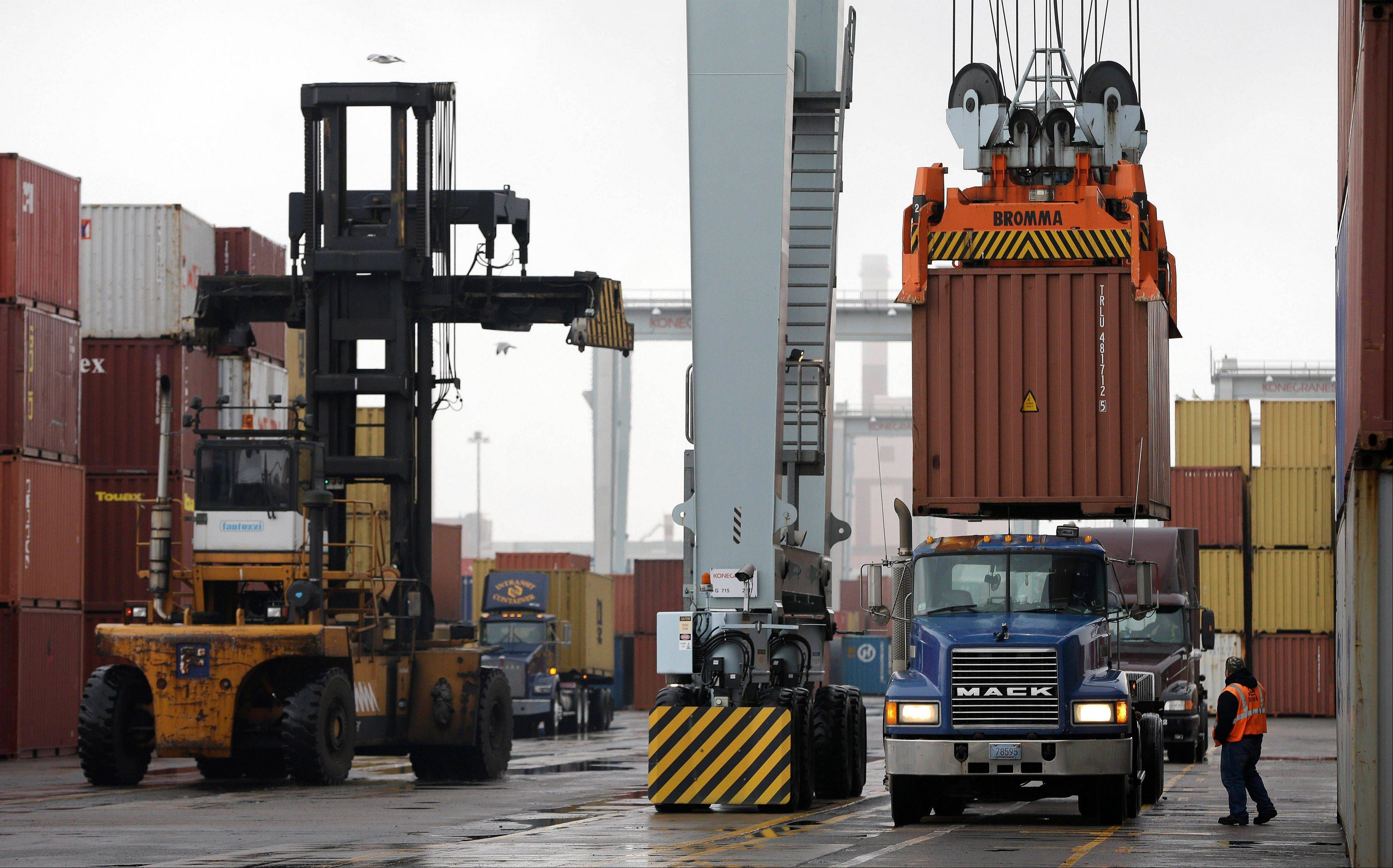 A truck driver watches as a freight container, right, is lowered onto a tractor trailer by a container crane at the Port of Boston in Boston. The crane and a reach stacker, left, are operated by longshoremen at the port.