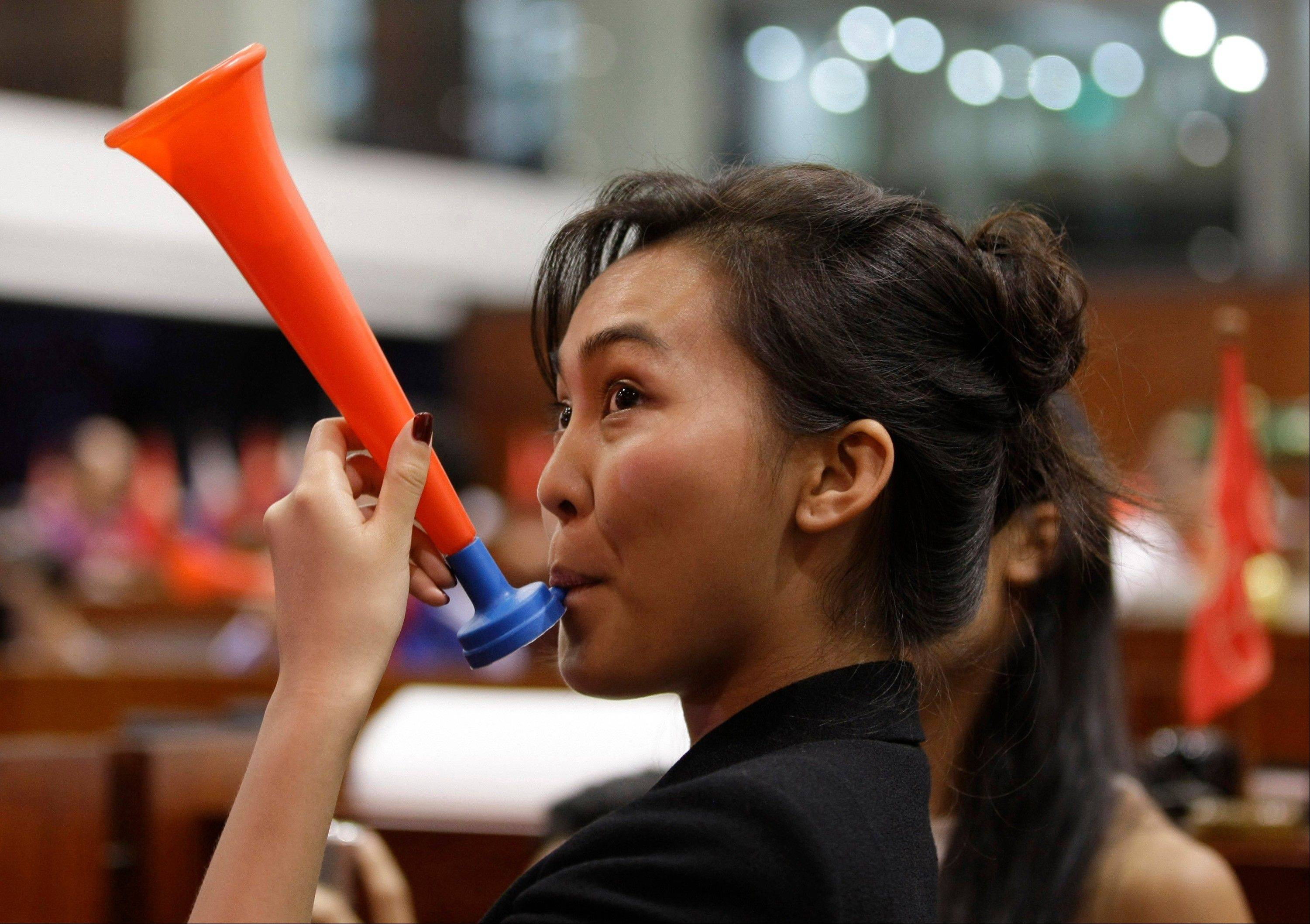 A Filipino trader blows a horn during the last day of trading this year at the Philippine Stock Exchange in the financial district of Makati, south of Manila, Philippines Friday.