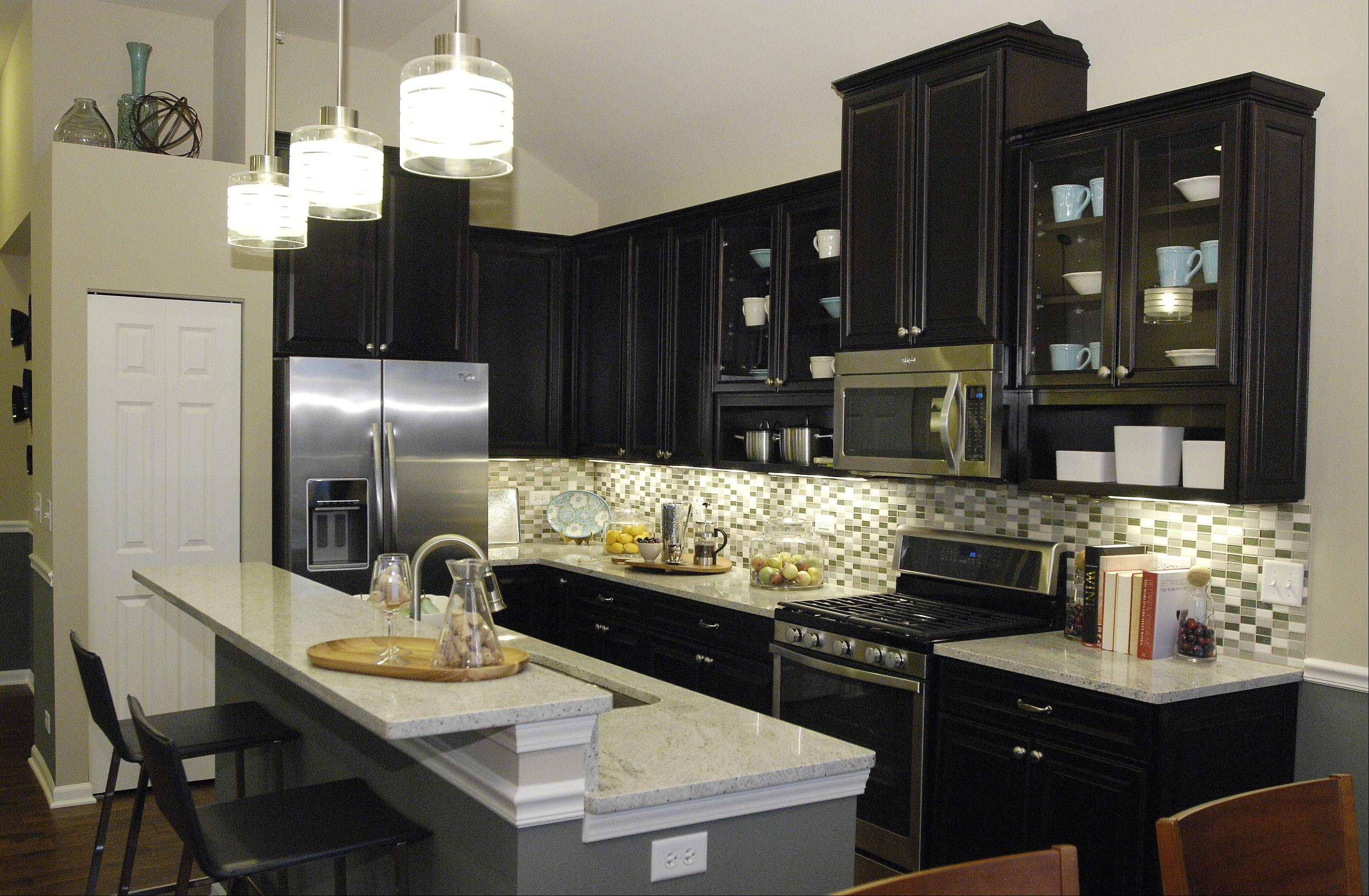 The Diversey model's kitchen sparkles with stainless steel appliances, granite countertops and mosaic tiles that create a decorative backsplash.