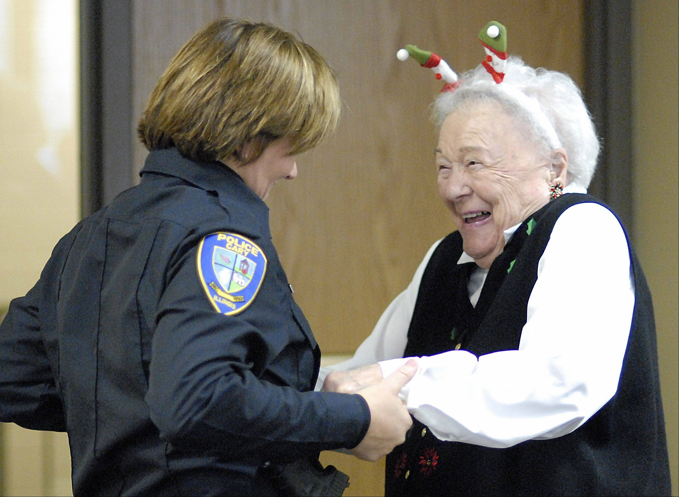"Edie Backman of Cary is greeted by Cary patrol officer and Elderly Service Officer Kathy Eiring during the Kraus Senior Center's Christmas party on Dec. 14. The two have been friends for the past few years, and Eiring continues to visit Backman who has recently moved from her home to an assisted living facility. ""Whenever she shows up at the senior center, I'm real happy,"" says Backman, ""(She's) a friend to everybody, a good officer."""
