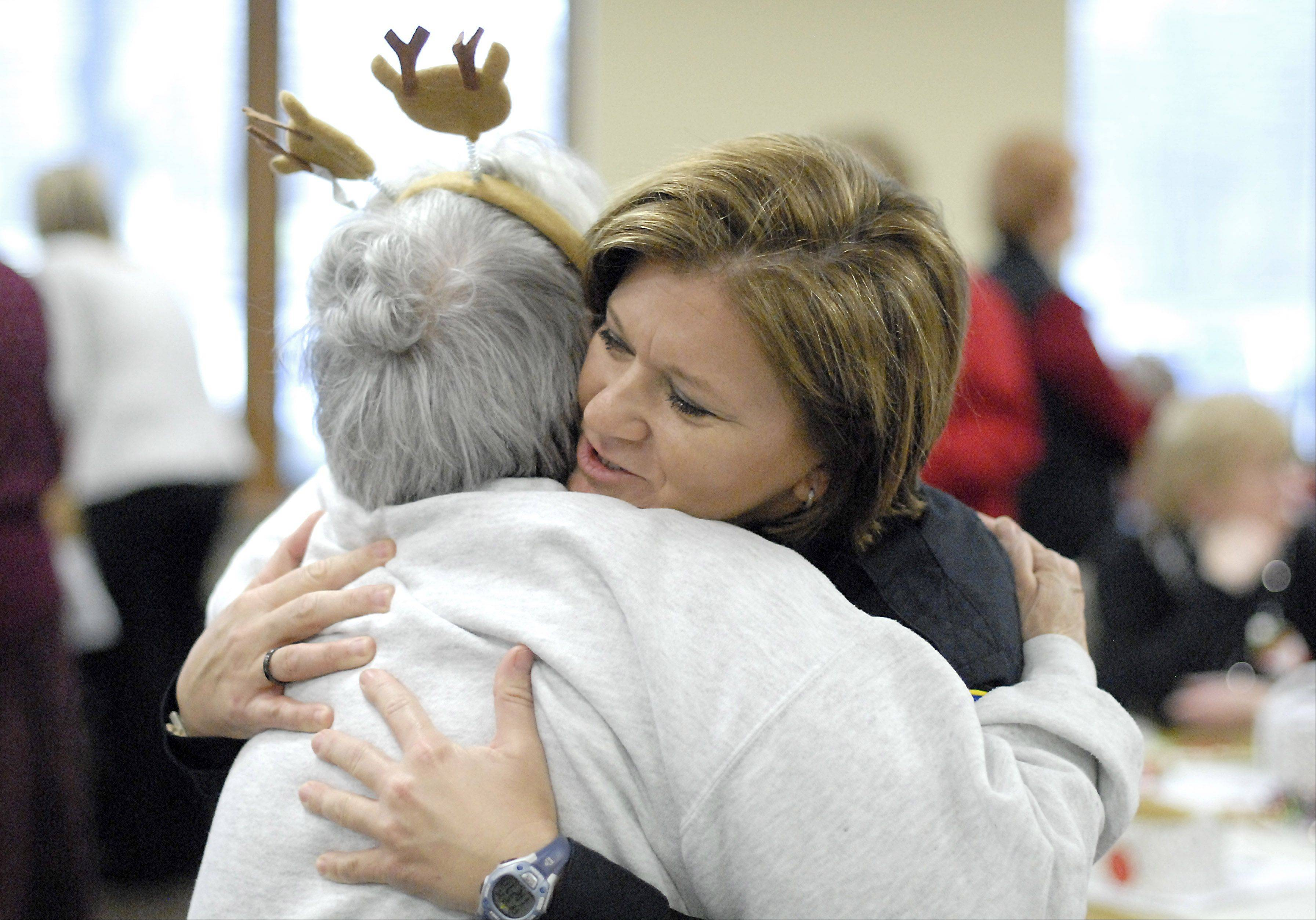 "Barbara Matson of Cary greets Cary patrol officer Kathy Eiring with ""Hello, sweetness!"" as she give her a big hug during the Kraus Senior Center's Christmas party. Matson, who has known Eiring for years, calls her a ""gift, a real gift."""