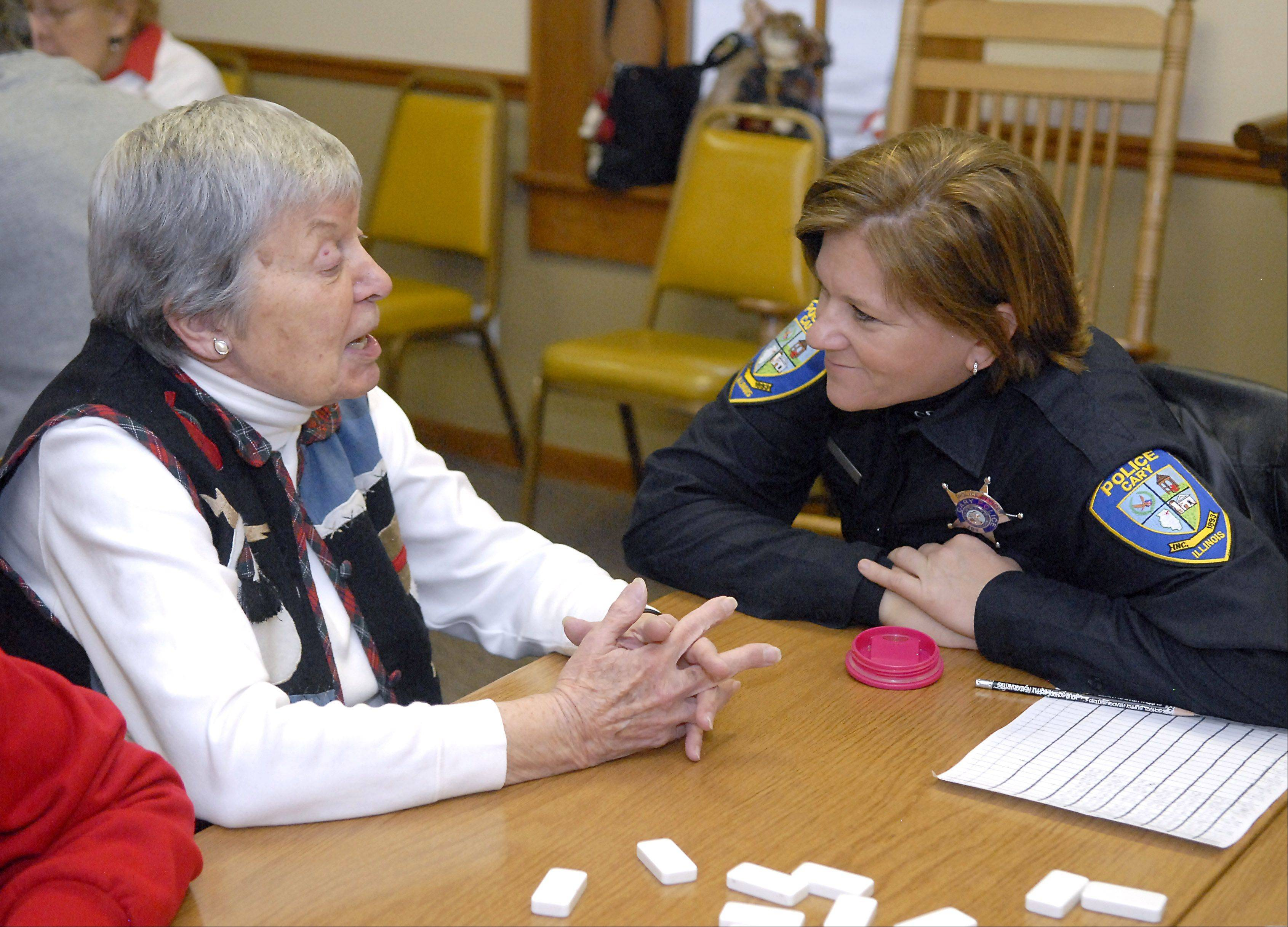 Officer Kathy Eiring chats with Beverly Kolpacke of Cary between Kolpacke's dominoes games at the Kraus Senior Center in Cary. Eiring visits the center at least once a week, sometimes more and even on her days off. The two have known each other for about five years.