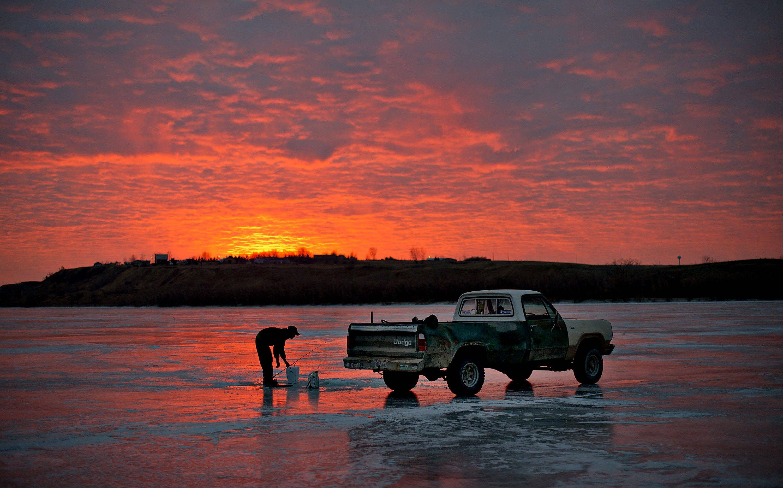 Joe Jessop, a truck driver from Orderville, Utah, sets his pole as while fishing on the frozen Missouri River in Williston, North Dakota, U.S., on Sunday, Feb. 12, 2012. North Dakota will hold its Republican presidential caucus on March 6.