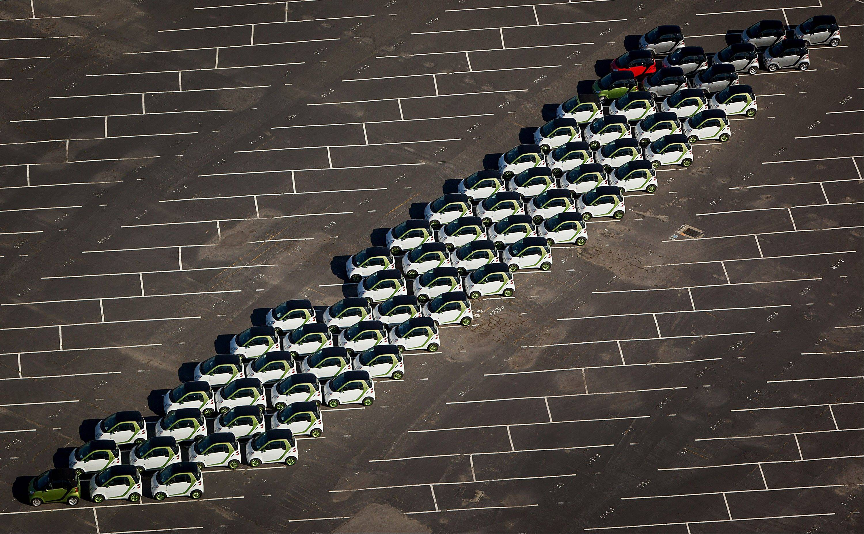 Daimler AG Smart Car vehicles sit lined up for dealer delivery at a distribution center outside the Port of Long Beach in Long Beach, California, U.S., on Tuesday, April 3, 2012. Job gains and buyers who put off car purchases during the recession are driving the fastest three-month auto-sales pace in four years, even as average U.S. unleaded gasoline prices rose 20 percent this year through the end of March.
