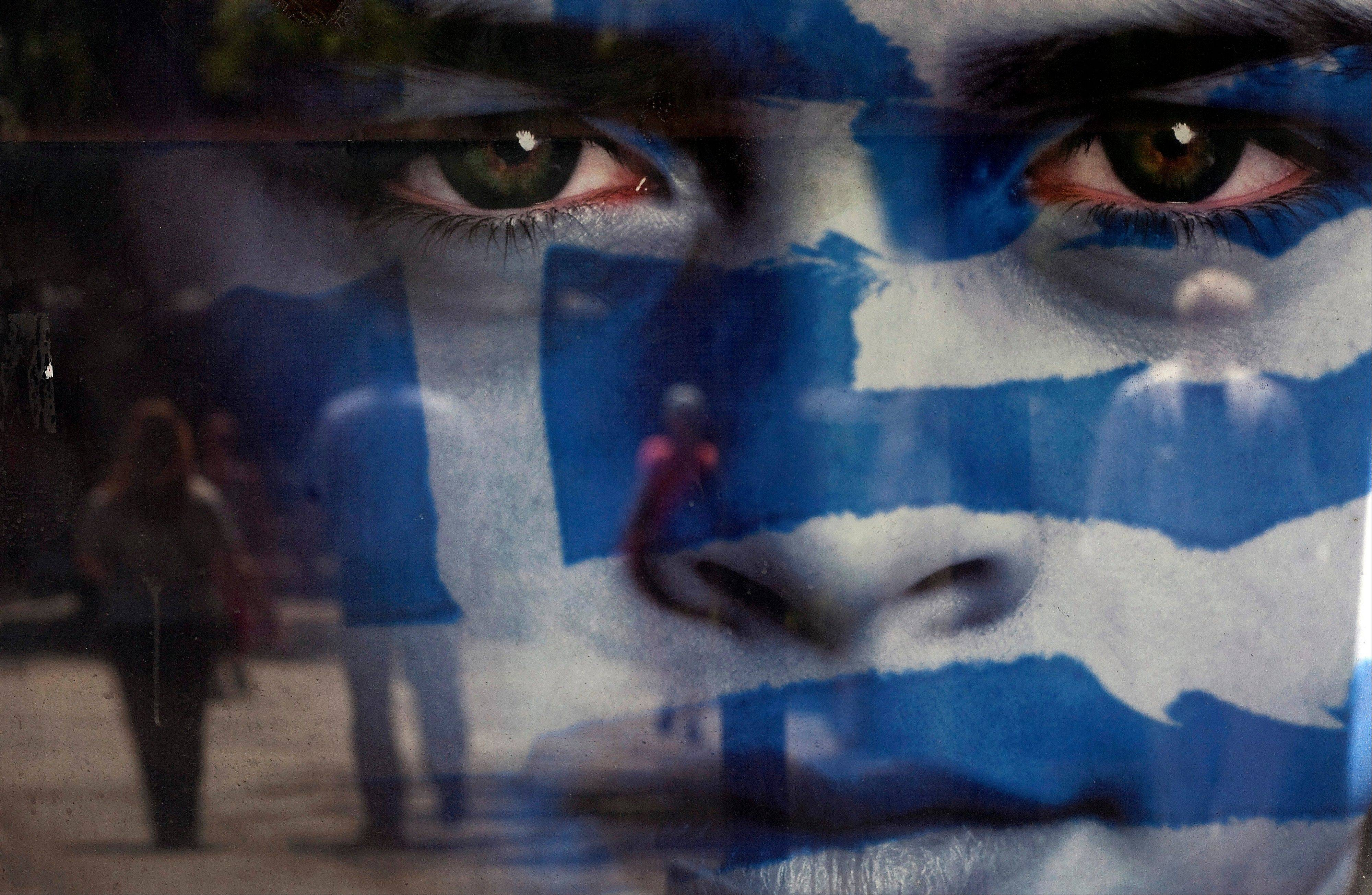 Pedestrians are reflected in a poster advertising the Greek national elections, on the day of voting in Athens, Greece, on Sunday, May 6, 2012. Greeks are voting today in national elections that may determine whether the country has a future in the euro area.