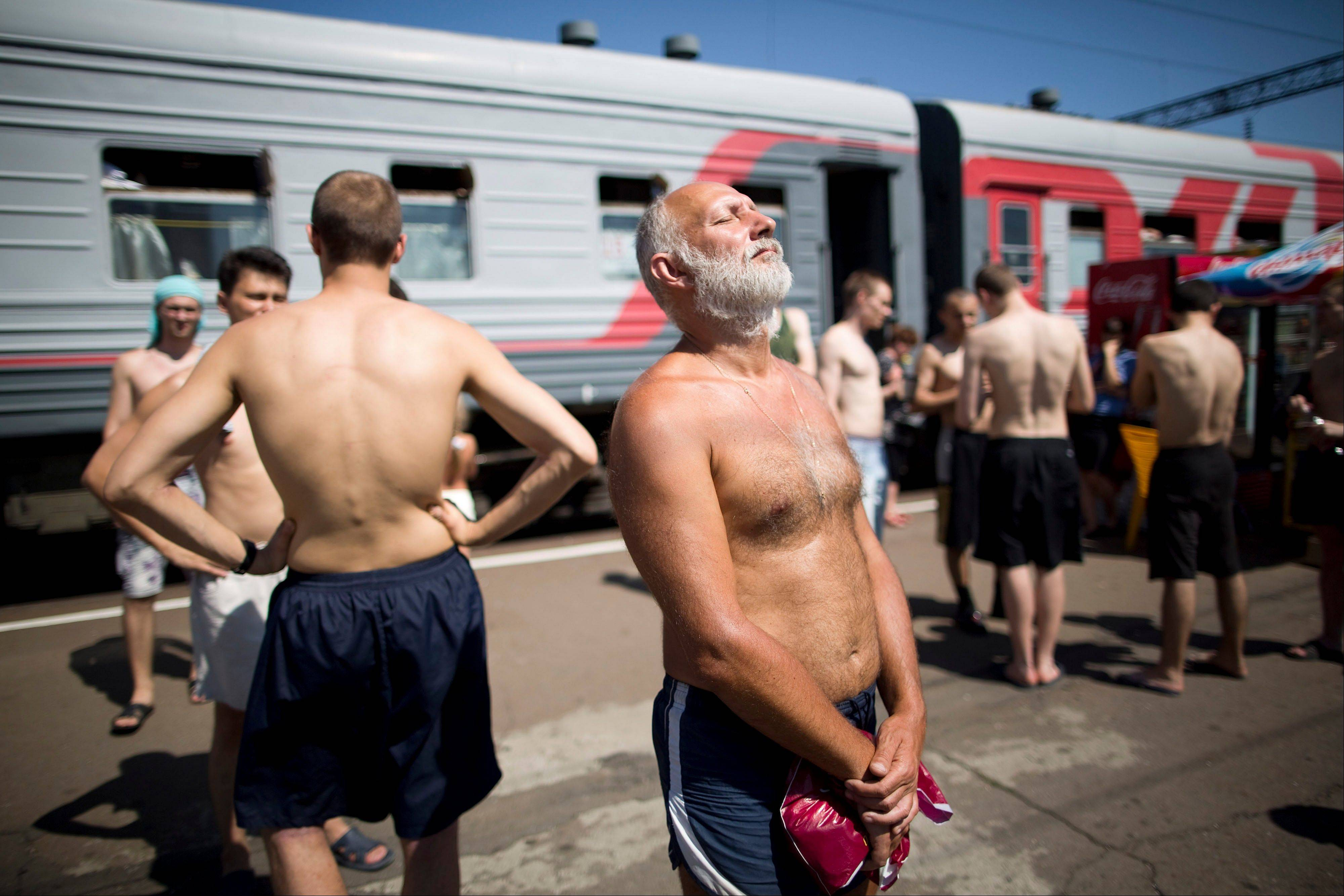 Passengers from the Novorossiysk-Moscow train, operated by OAO Russian Railways, sunbathe on a platform at Liski station in Voronezh region, Russia, on Sunday, July 15, 2012. Russia's government plans to sell stakes in its rail monopoly, grain trader, biggest shipper, nanotechnology holding and largest banks within 18 months as it loosens its grip on an economy dominated by commodity exports.