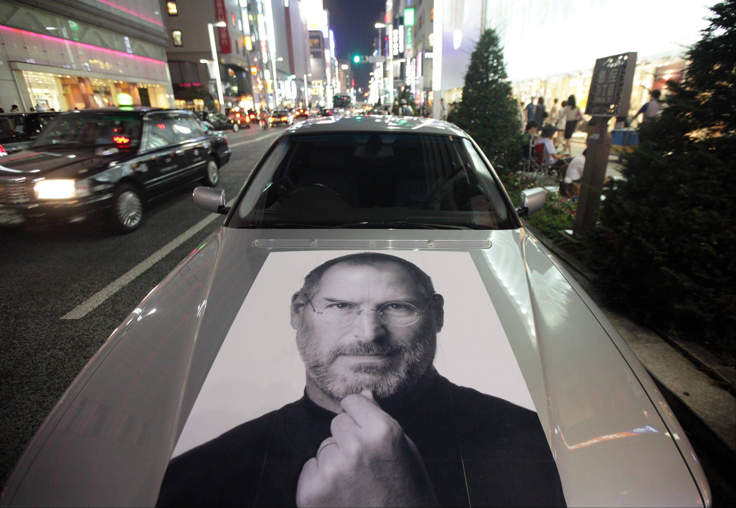 A car bearing a photograph of Steve Jobs, late chief executive officer of Apple Inc., is parked outside the Apple store at night in the Ginza district of Tokyo, Japan, on Thursday, Sept. 20, 2012. Apple's iPhone 5, which features a bigger screen, faster chip and a lighter body, sold 2 million units in first-day orders, more than double a record set by the previous model, Apple said.