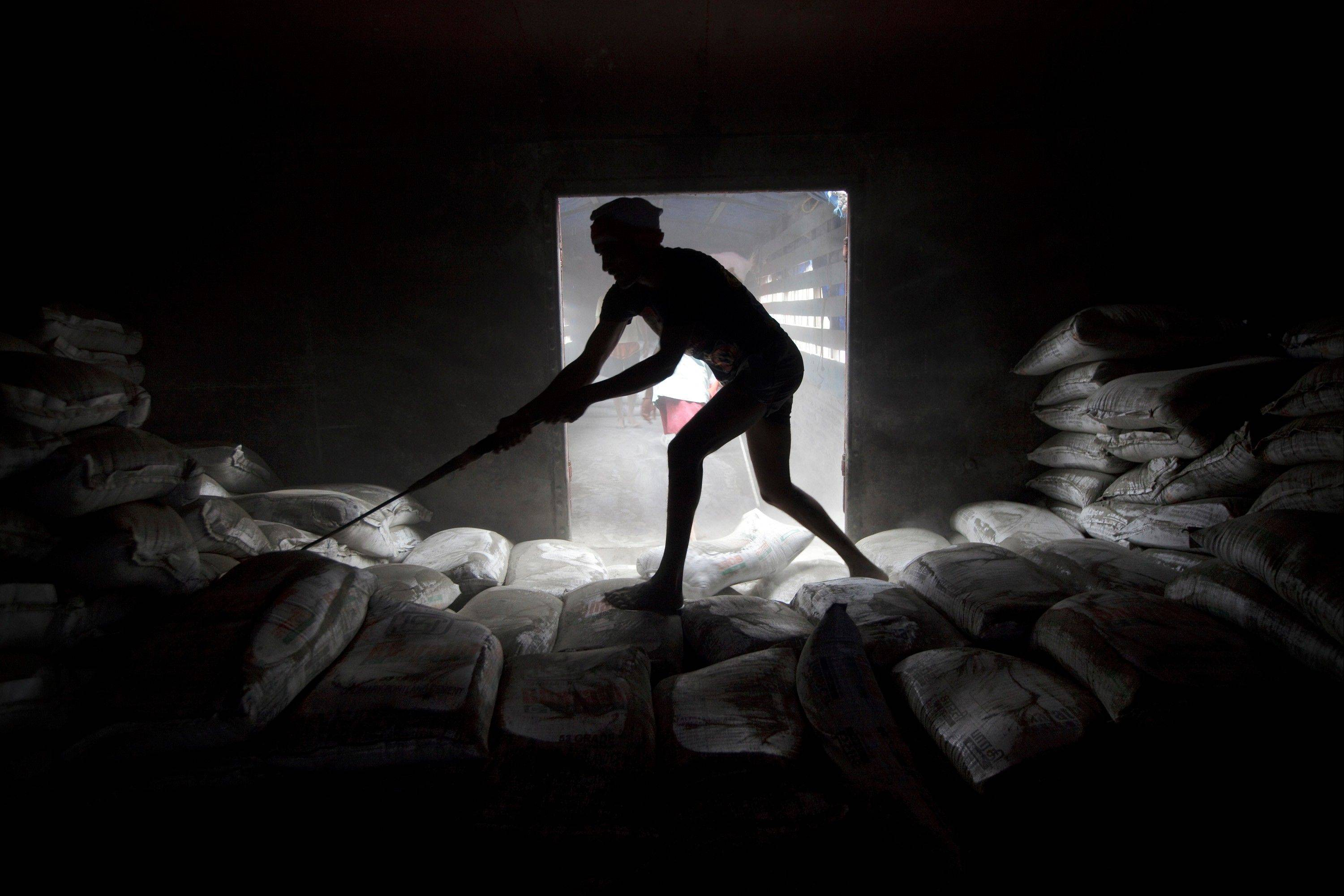 A worker unloads sacks of cement from a freight train in Mumbai, India, on Tuesday, Sept. 11, 2012. India, Asia's third-largest economy, grew 5.5 percent in the three months ended June 30 after expanding 5.3 percent in the previous quarter, the least in three years.