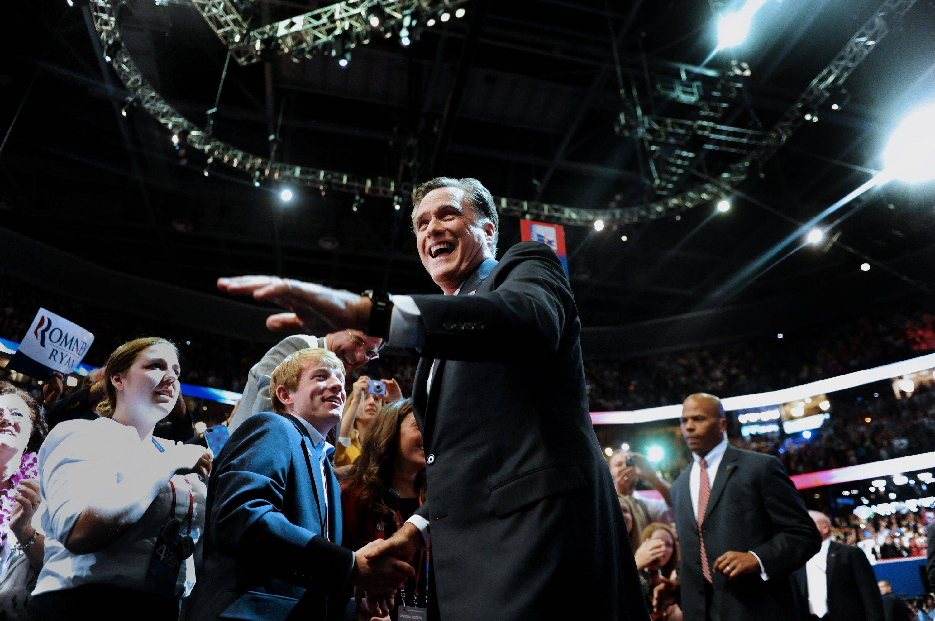 Mitt Romney, Republican presidential candidate, waves while greeting delegates before speaking at the Republican National Convention (RNC) in Tampa, Florida, U.S., on Thursday, Aug. 30, 2012. Romney, a wealthy former business executive who served as Massachusetts governor and as a bishop in the Mormon church, is under pressure to show undecided voters more personality and emotion in his convention speech tonight, even as fiscal conservatives in his own party say he must more clearly define his plans for reining in the deficit and improving the economy.