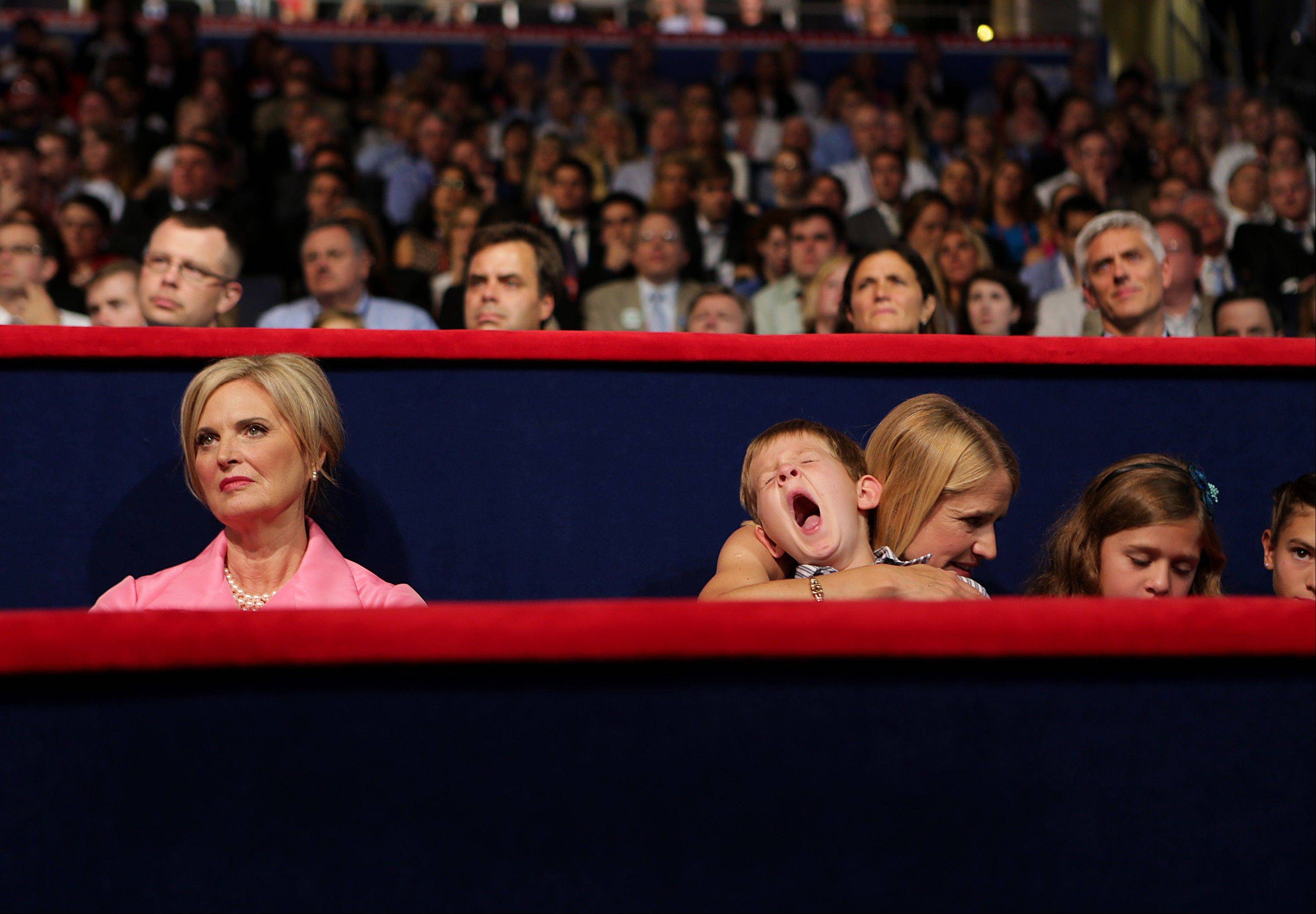 Ann Romney, wife of Republican presidential candidate Mitt Romney, left, sits with Janna Ryan, wife of Republican vice presidential candidate Paul Ryan, as she holds her yawning son Sam Ryan at the Republican National Convention (RNC) in Tampa, Florida, U.S., on Wednesday, Aug. 29, 2012. Representative Paul Ryan takes the stage tonight to address the RNC with a dual mission: to provide a spark, along with his big ideas about cutting the budget, to energize the party's base.