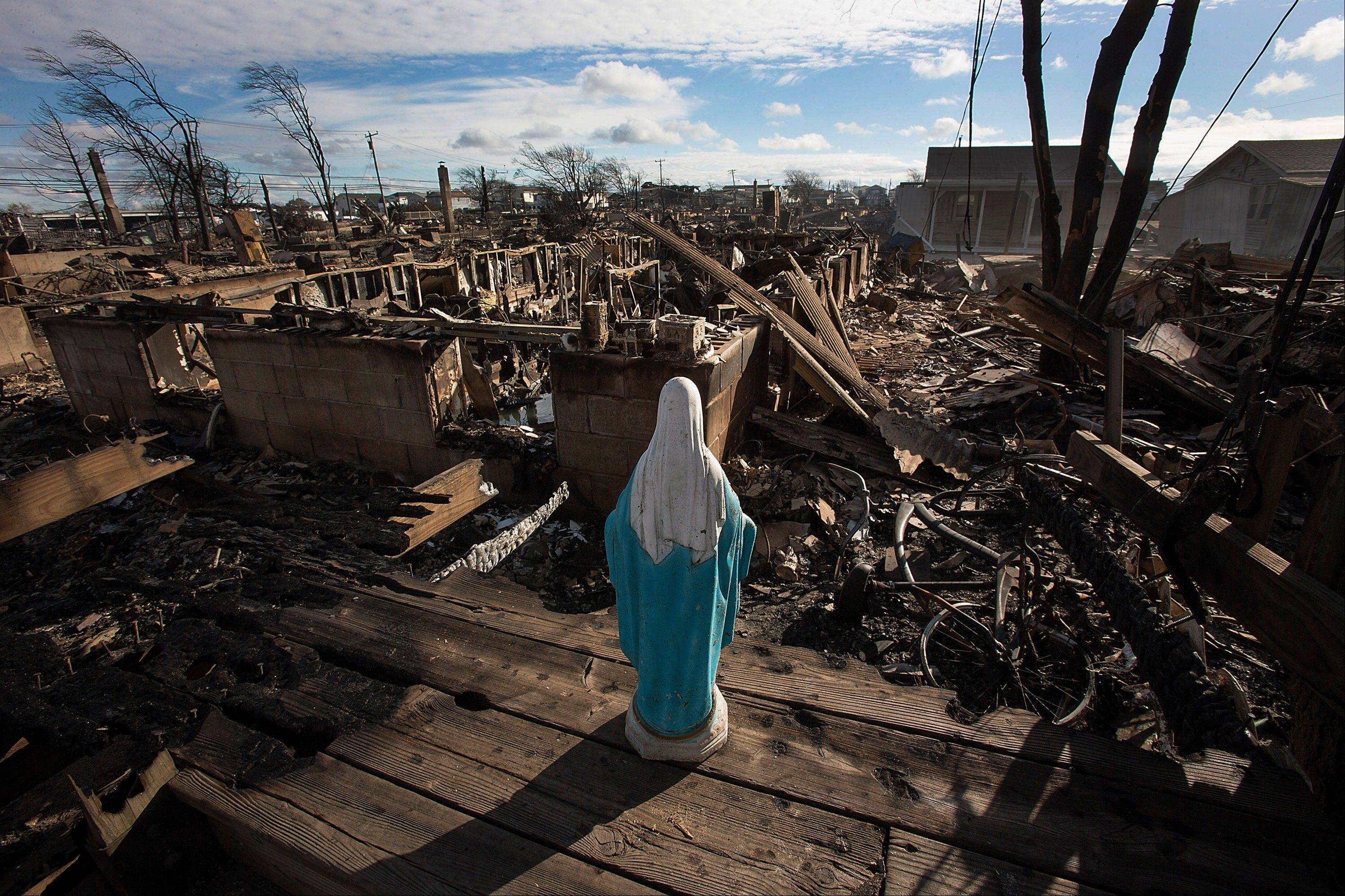 A statue of the Virgin Mary stands over houses destroyed by fire in the Breezy Point neighborhood of the Queens borough of New York, U.S., on Wednesday, Oct. 31, 2012. Atlantic superstorm Sandy may cut U.S. economic growth as it keeps millions of employees away from work and shuts businesses from restaurants to refineries in one of the nation�s most populated and productive regions.