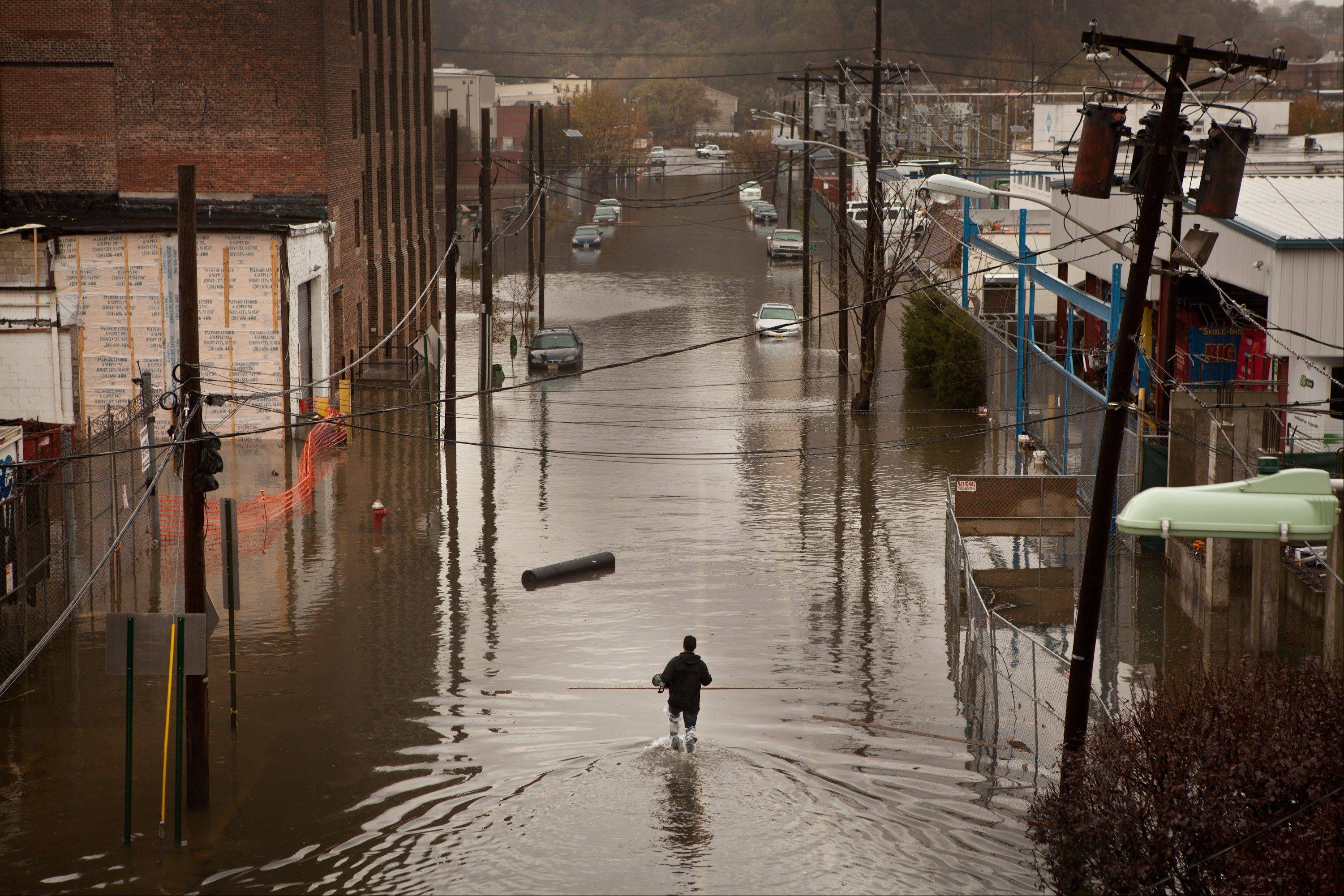 A man walks through flood waters in Hoboken, New Jersey, U.S., on Tuesday, Oct. 30, 2012. The Atlantic storm Sandy left a landscape of devastation across much of New Jersey, tearing apart seaside resort towns, ripping houses from foundations and littering the turnpike with rail cars and debris.