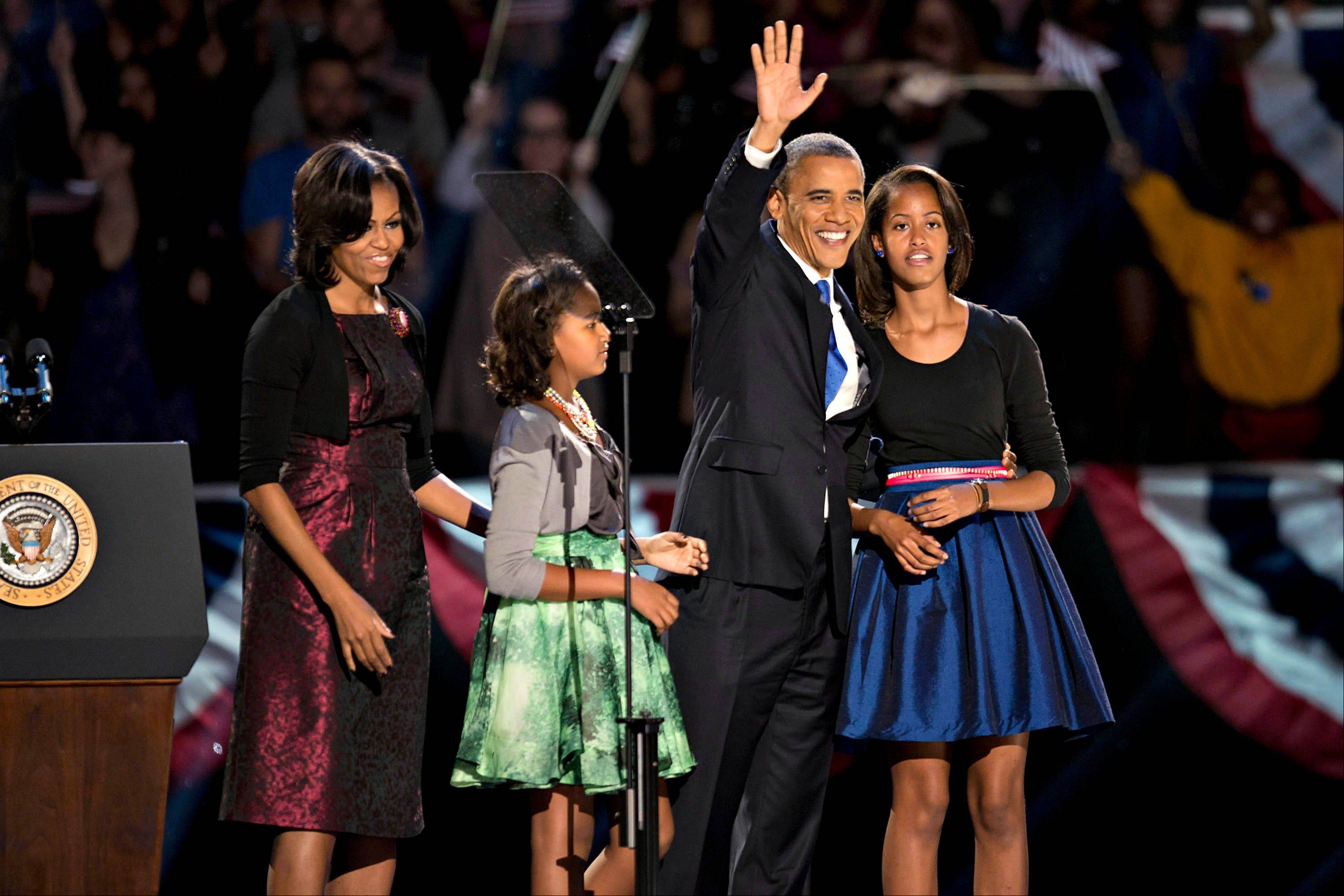 U.S. President Barack Obama stands on stage with his wife Michelle Obama, left, and daughters Sasha, second left, and Malia, right, before making an acceptance speech during an election night rally in Chicago, Illinois, U.S., in the early morning on Wednesday, Nov. 7, 2012. Obama, the post-partisan candidate of hope who became the first black U.S. president, won re-election today by overcoming four years of economic discontent with a mix of political populism and electoral math.
