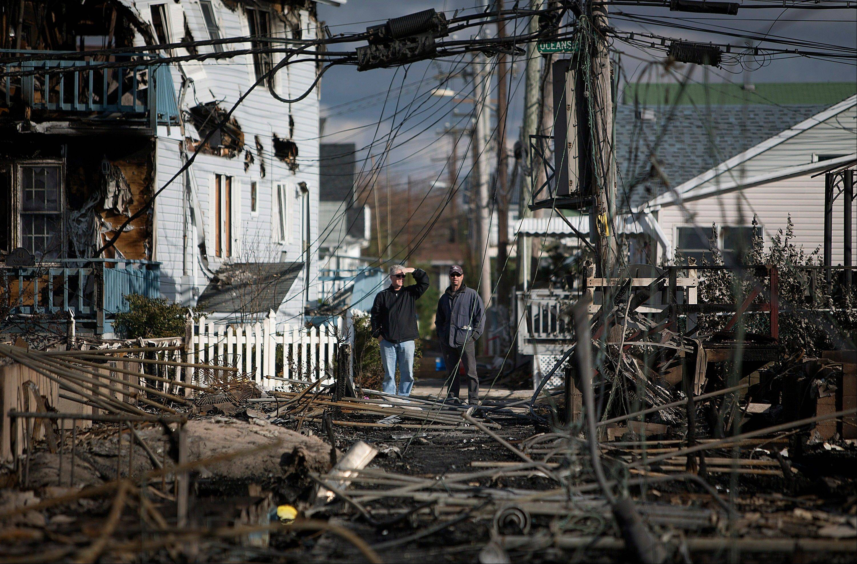 Residents look over the damage in the Breezy Point neighborhood of the Queens borough of New York, U.S., on Wednesday, Oct. 31, 2012. Atlantic superstorm Sandy may cut U.S. economic growth as it keeps millions of employees away from work and shuts businesses from restaurants to refineries in one of the nation�s most populated and productive regions.
