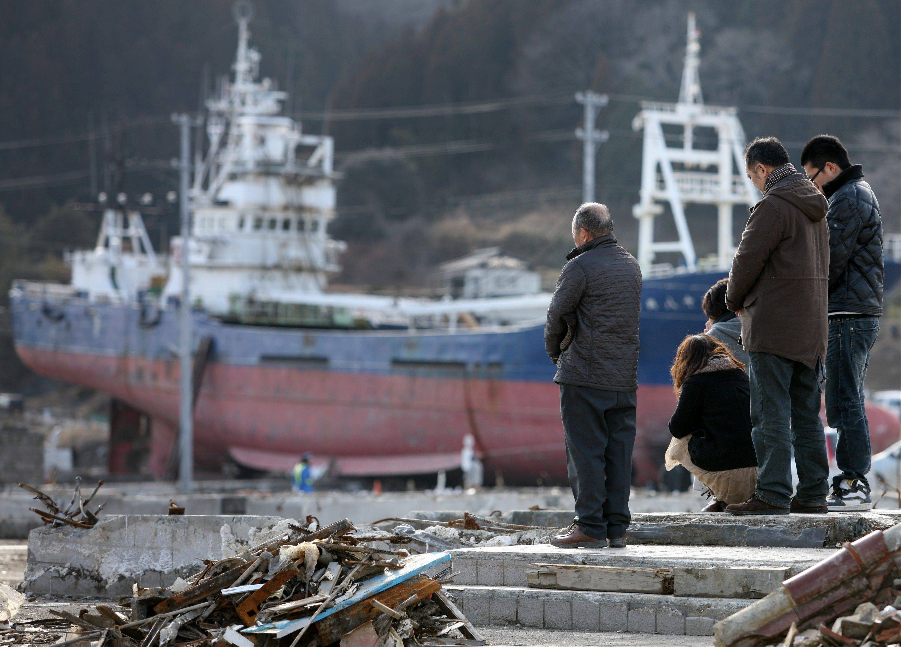 People observe a moment of silence in front of a vessel swept inland by the tsunami which followed the Great East Japan Earthquake to commemorate the one-year anniversary of the disaster at 2:46 p.m. in Kesennuma City, Miyagi Prefecture, Japan, on Sunday, March 11, 2012. The magnitude-9 earthquake last year triggered a tsunami that in just 60 minutes laid waste to entire towns, engulfed four-story hospitals, left hundreds of thousands of homeless and crippled a nuclear plant.