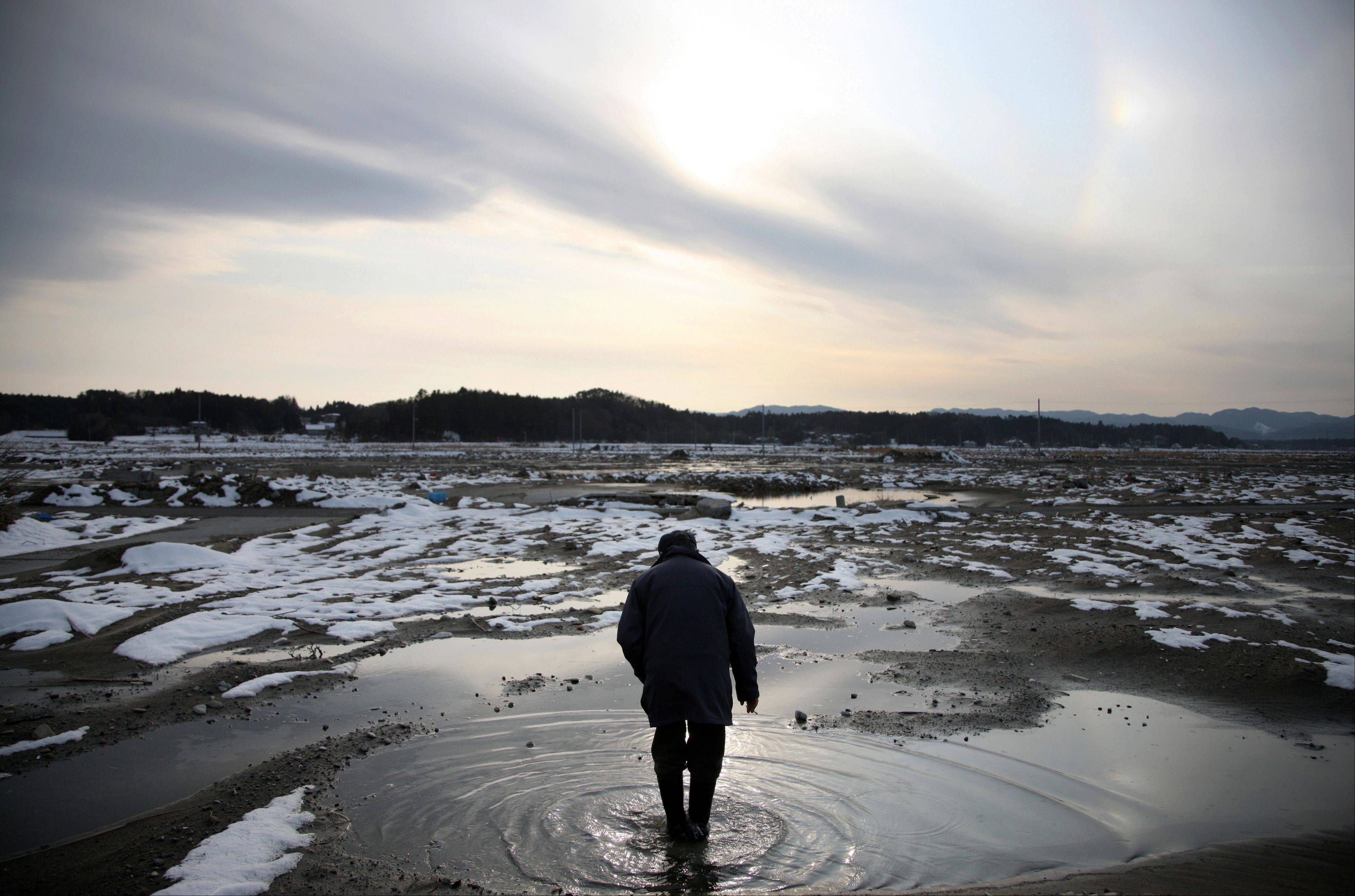 Kazushige Hayashi walks through puddles of water at the site of where his house stood before the March 11 earthquake and tsunami in Minamisoma City, Fukushima Prefecture, Japan, on Sunday, March 4, 2012. Japan marks the one-year anniversary of the earthquake and tsunami this month for the 15,845 dead and the 3,368 still missing.