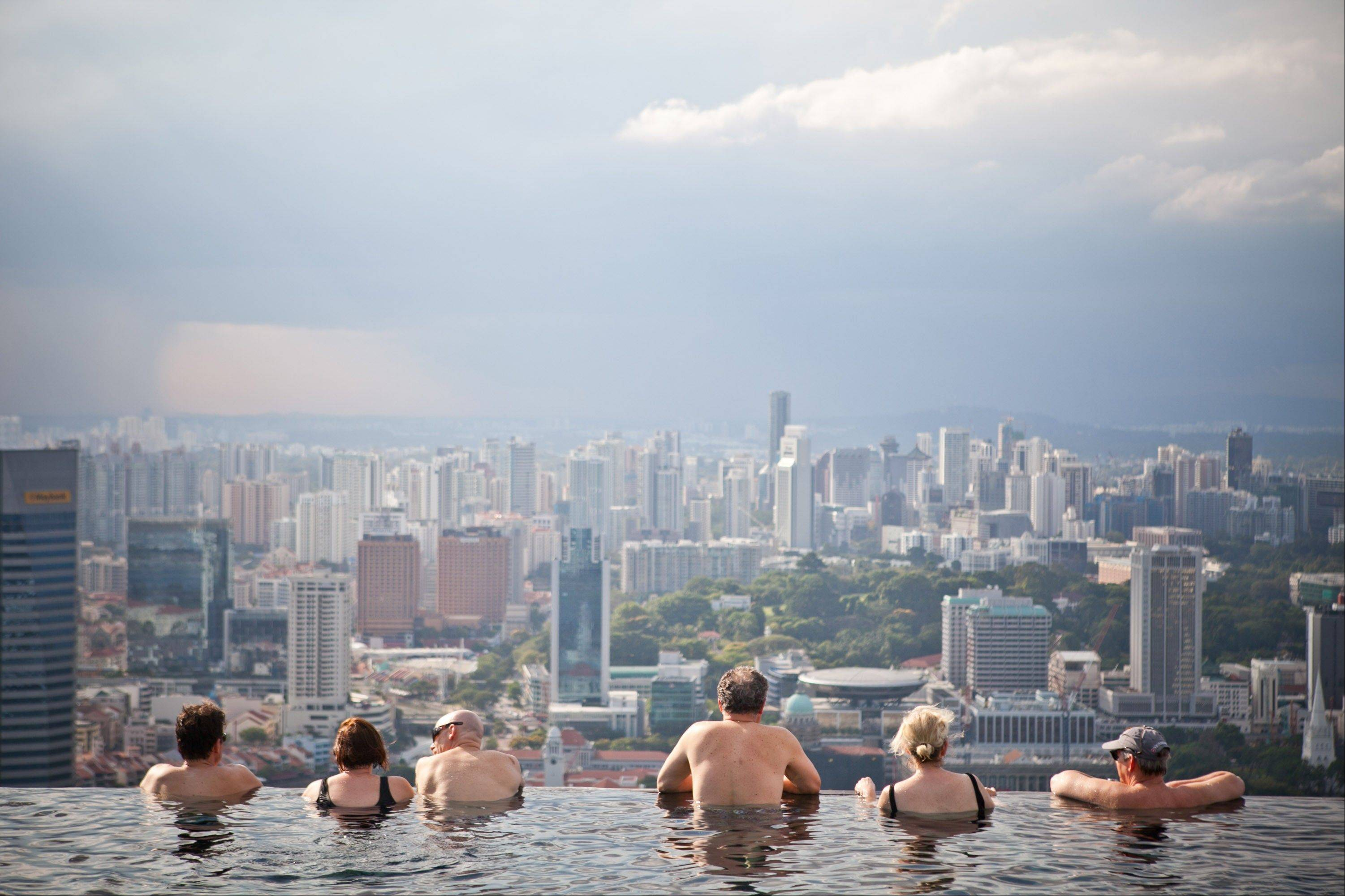 Hotel guests in the infinity pool at the SkyPark atop Marina Bay Sands look out towards the city skyline in Singapore, on Tuesday, Feb. 28, 2012. The number of visitors to the island rose to a record 13.2 million in 2011 as casino-resorts run by Genting Singapore Plc and Las Vegas Sands Corp. lured tourists.
