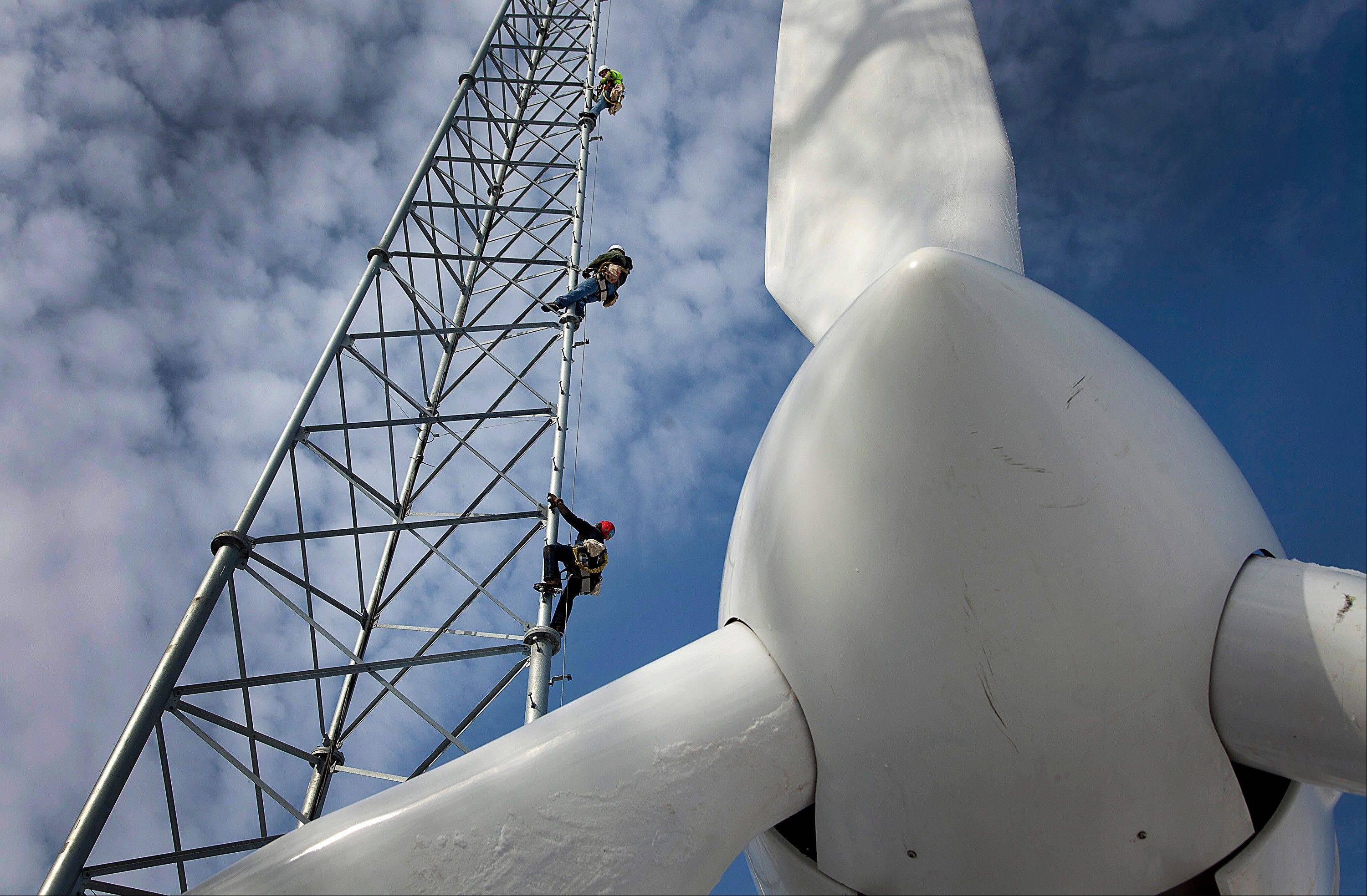 Dietz Brothers Inc. tower men Jonathan Thompson, from bottom, Ben Christianson, and Jake Bengtson climb a Polaris Industries Inc. wind turbine installed by Renewable Energy SD in Elgin, Minnesota, U.S., on Wednesday, Feb. 15, 2012. The U.S. wind and solar energy industries need an extension of production tax credits, which are scheduled to expire at the end of the year, Energy Secretary Steven Chu said.