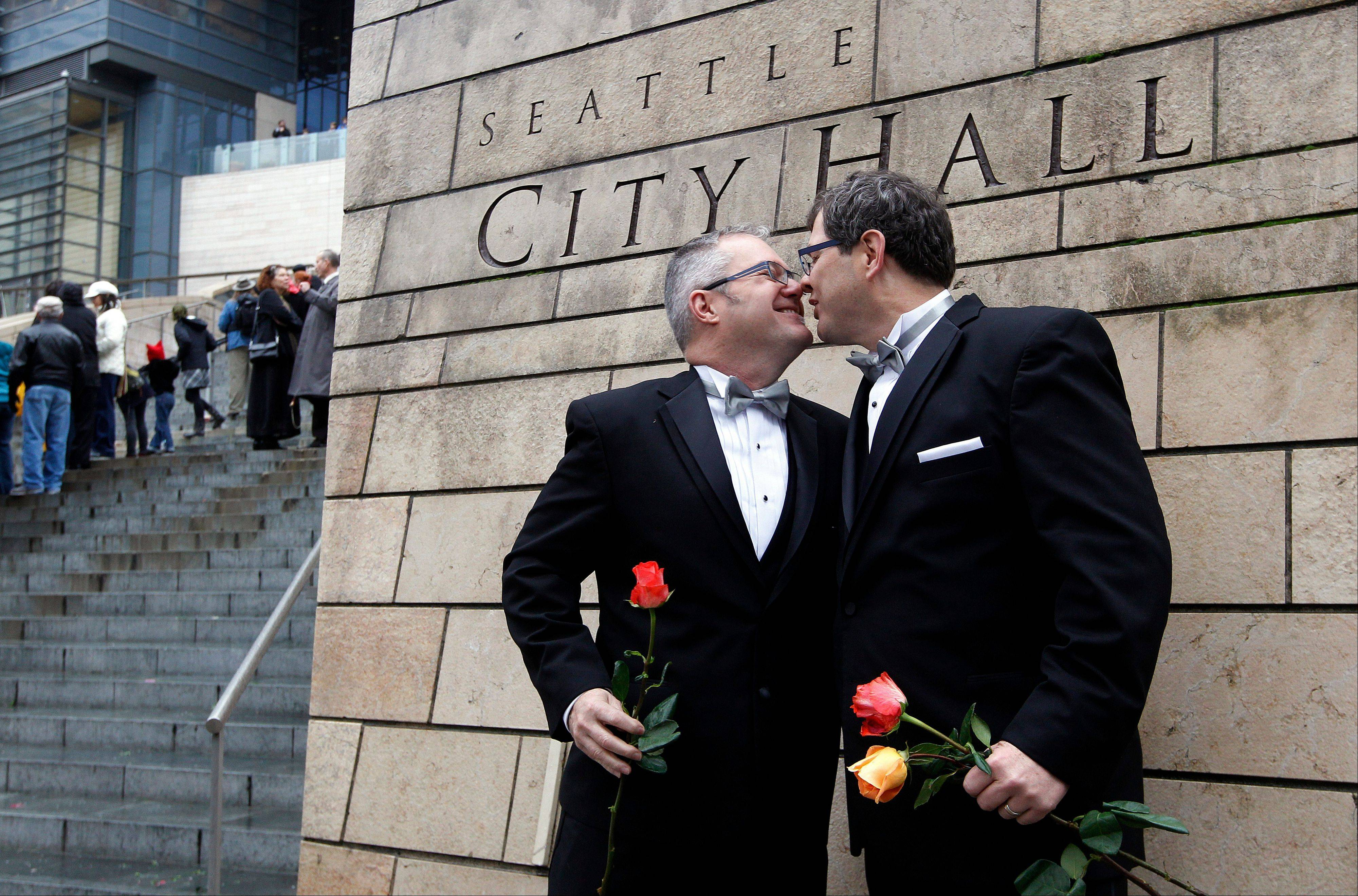 Terry Gilbert, left, kisses his husband Paul Beppler after wedding at Seattle City Hall, becoming among the first gay couples to legally wed in the state, Sunday, Dec. 9, 2012, in Seattle. Gov. Chris Gregoire signed a voter-approved law legalizing gay marriage Dec. 5 and weddings for gay and lesbian couples began in Washington on Sunday, following the three-day waiting period after marriage licenses were issued earlier in the week.