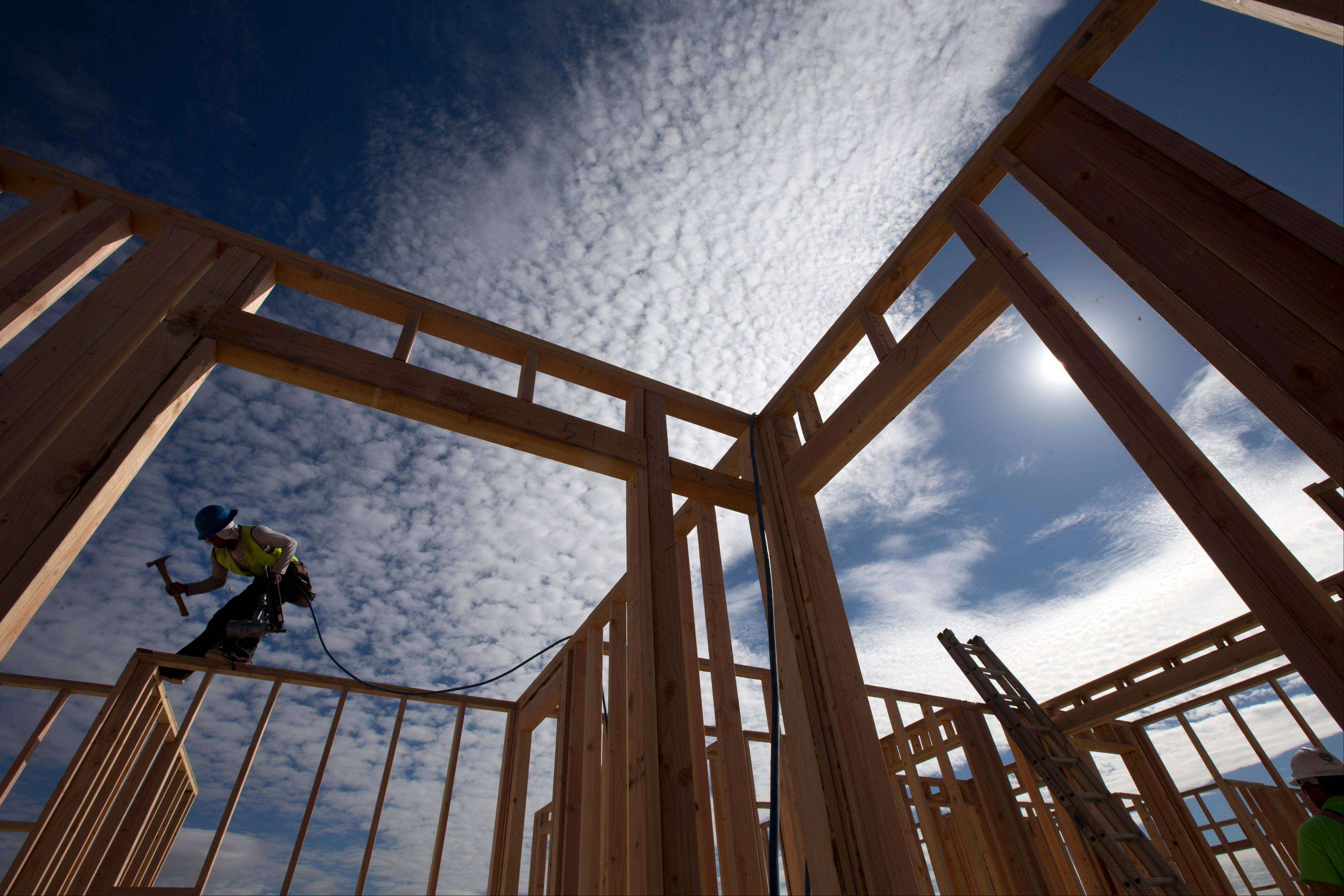 Construction worker Elabert Salazar works on a house frame for a new home in Chula Vista, Calif. In 2012, the unemployment rate dipped to a four-year-low of 7.7 percent, stock markets rose, builders broke ground on more homes, and November was the best sales month in nearly five years for U.S. automakers.