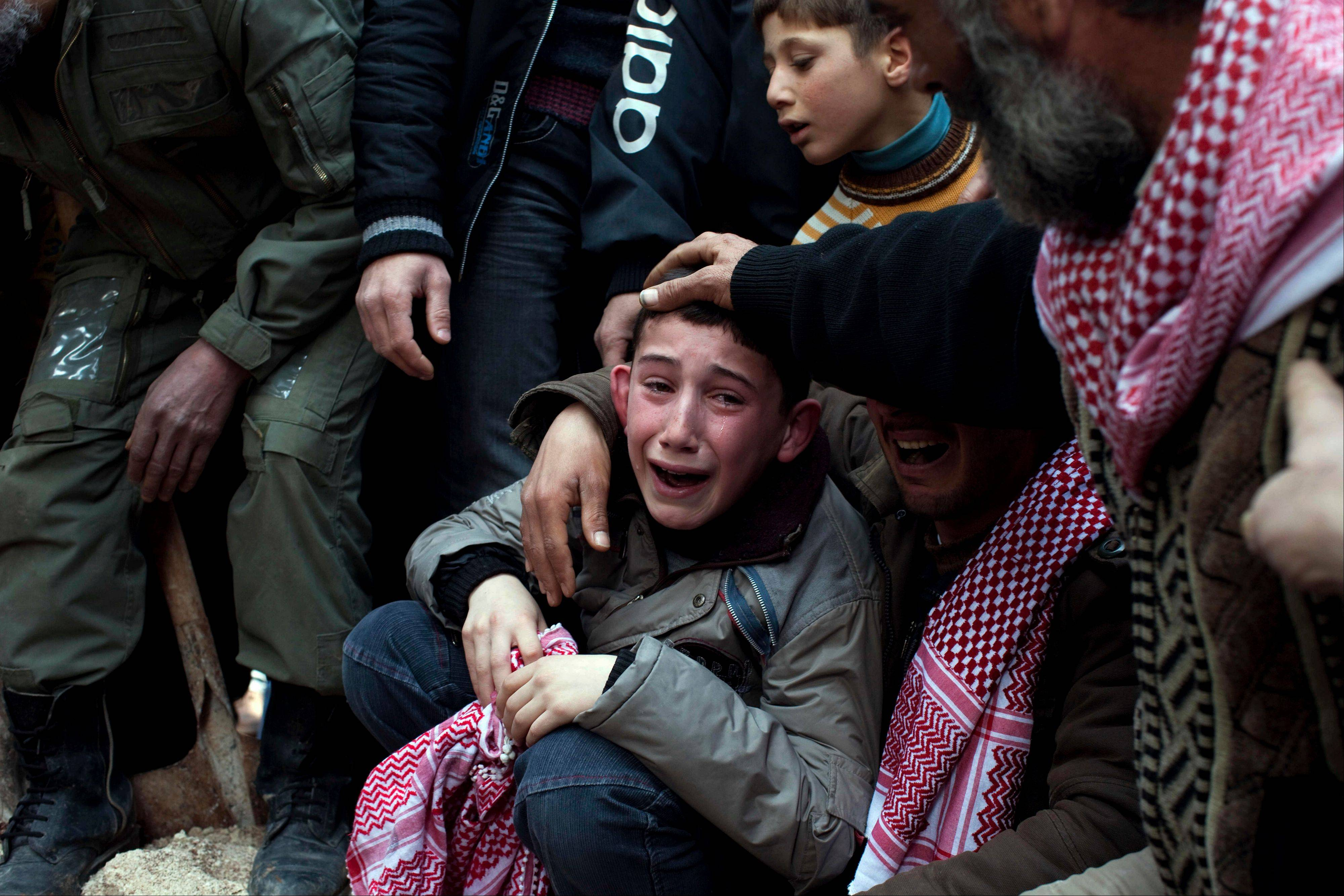 Ahmed, center, mourns his father Abdulaziz Abu Ahmed Khrer, who was killed by a Syrian Army sniper, during his funeral in Idlib, north Syria.