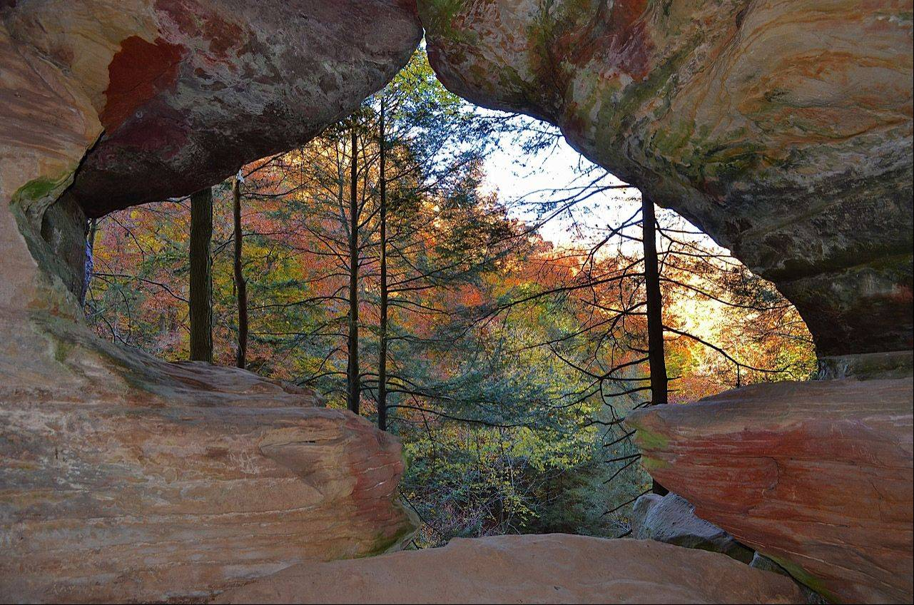 A cave opening showcases the color brilliance of the natural stone with the changing colors of the fall leaves this past October in Hocking Hills, Ohio.