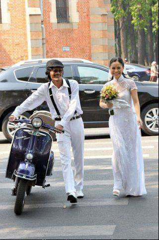 A couple walks their scooter down a street on their wedding day in Saigon, Vietnam.