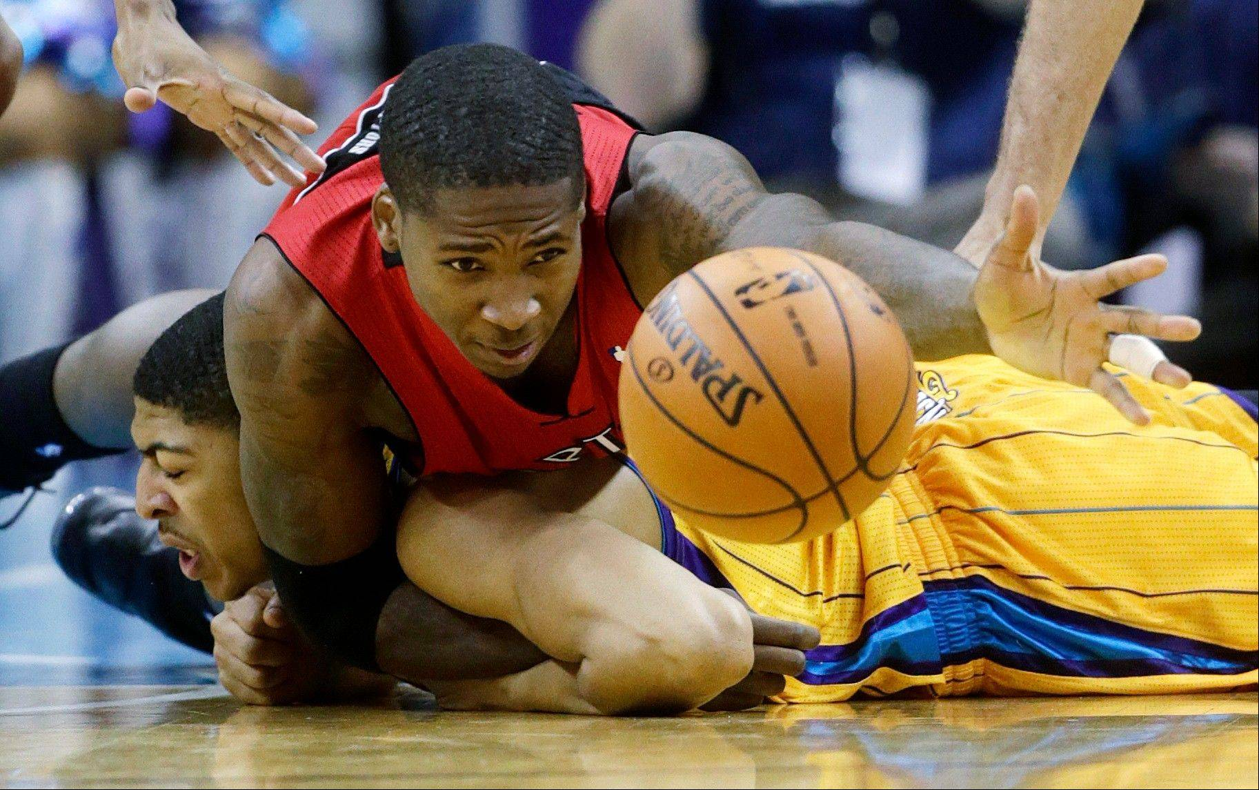 Raptors forward Ed Davis, top, fights for a loose ball with Hornets forward Anthony Davis during the third quarter Friday in New Orleans.