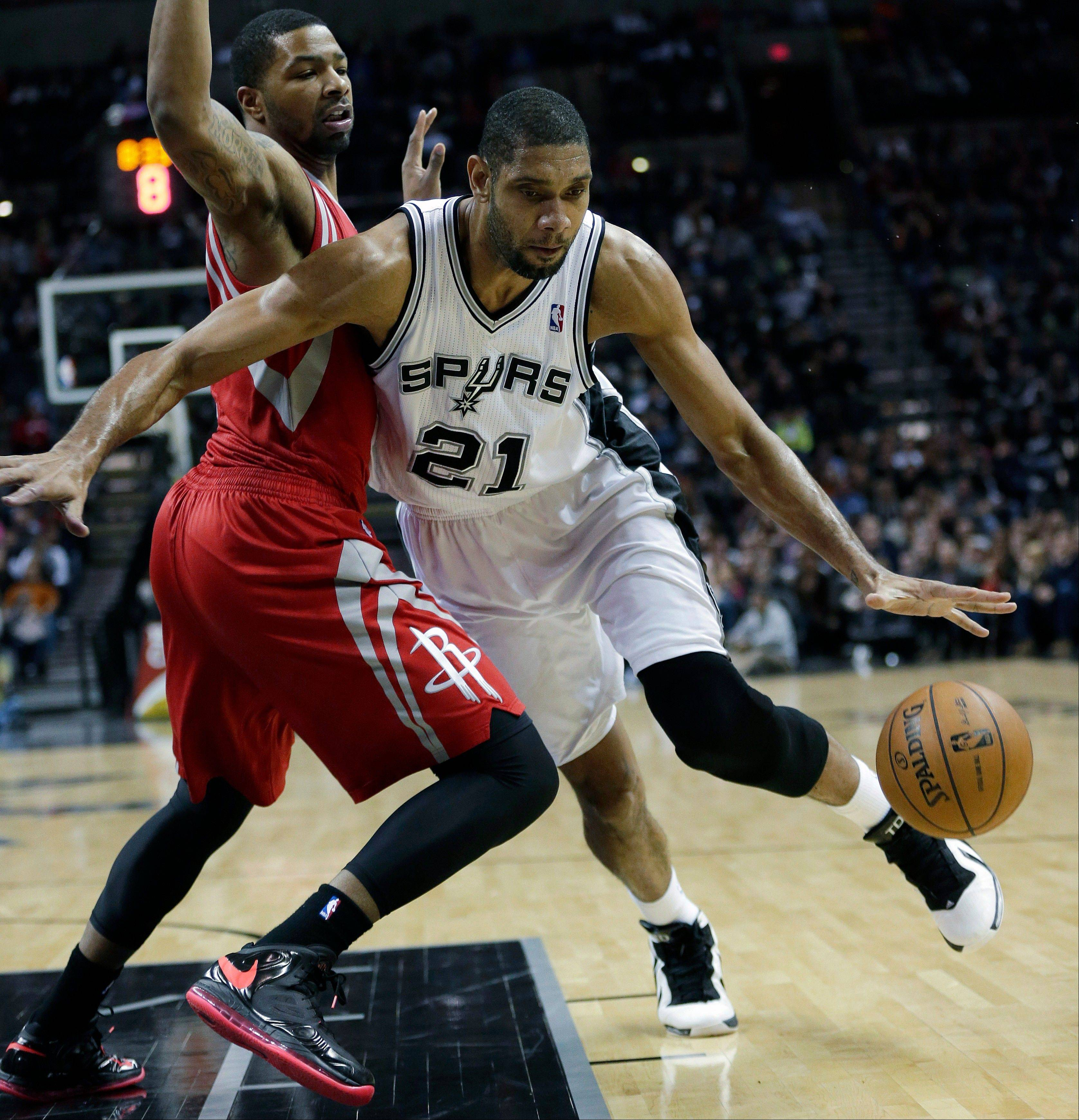 The Spurs' Tim Duncan (21) works the ball around Houston's Marcus Morris during the first quarter Friday in San Antonio.