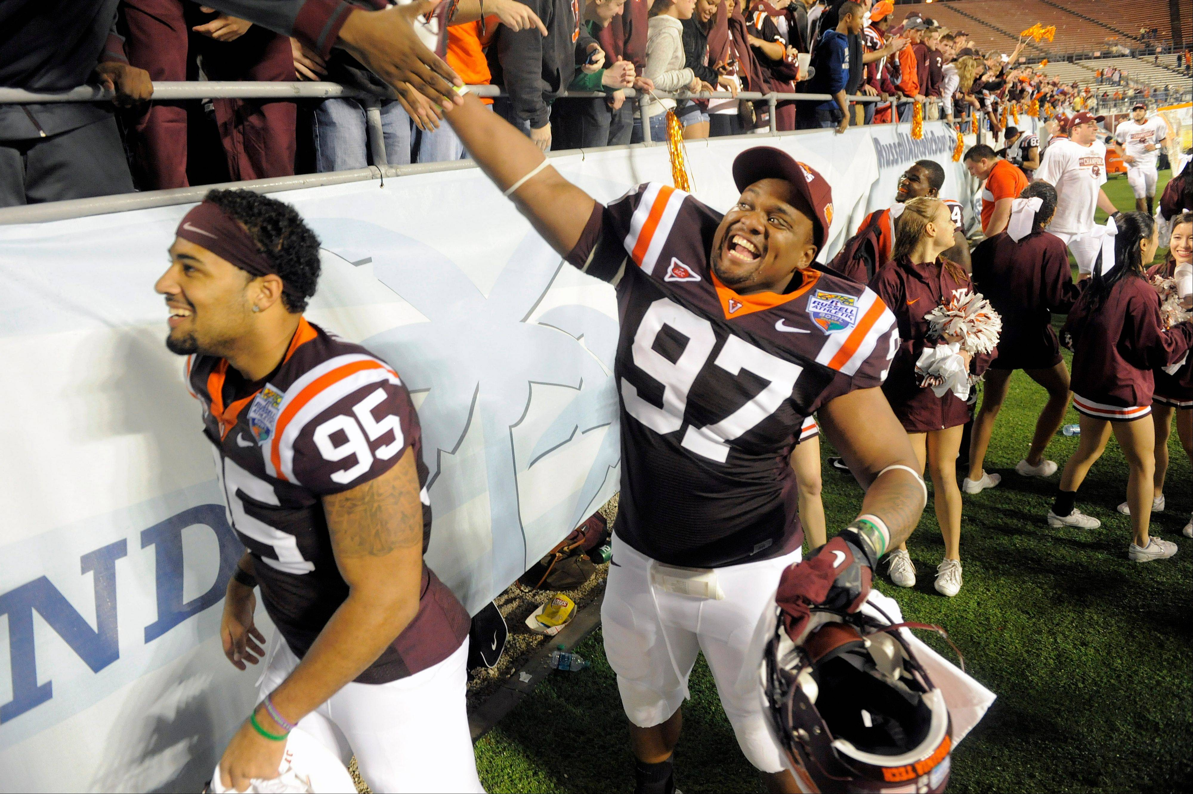 Virginia Tech defensives tackle Zack McCray, left, and Kris Harley, right, celebrate with fans Friday following their 13-10 win in overtime of the Russell Athletic Bowl game against Rutgers in Orlando, Fla.
