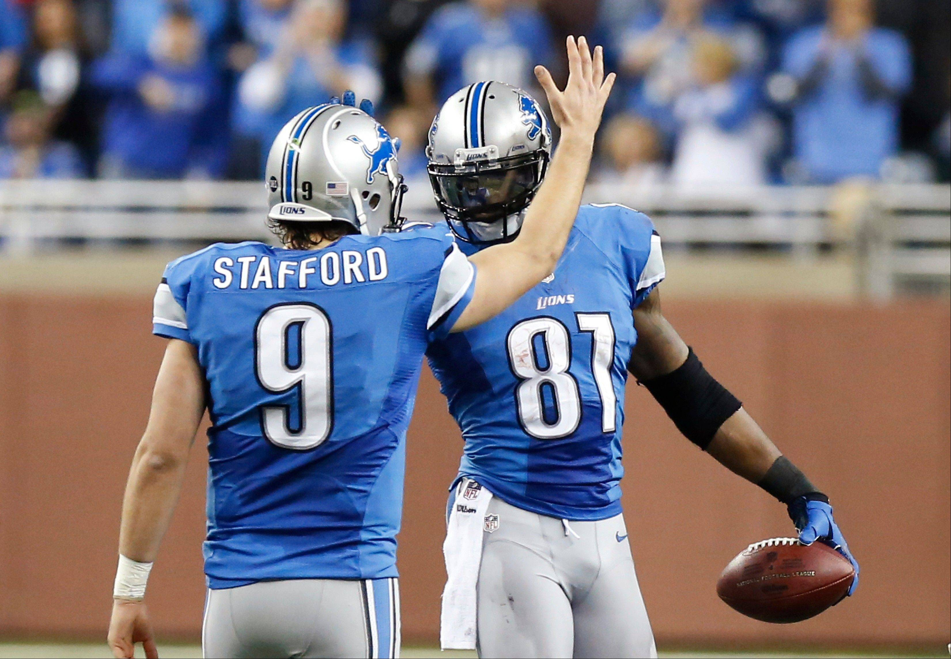 Calvin Johnson is congratulated by quarterback Matthew Stafford after he broke Jerry Rice's single-season record for receiving yards last week.