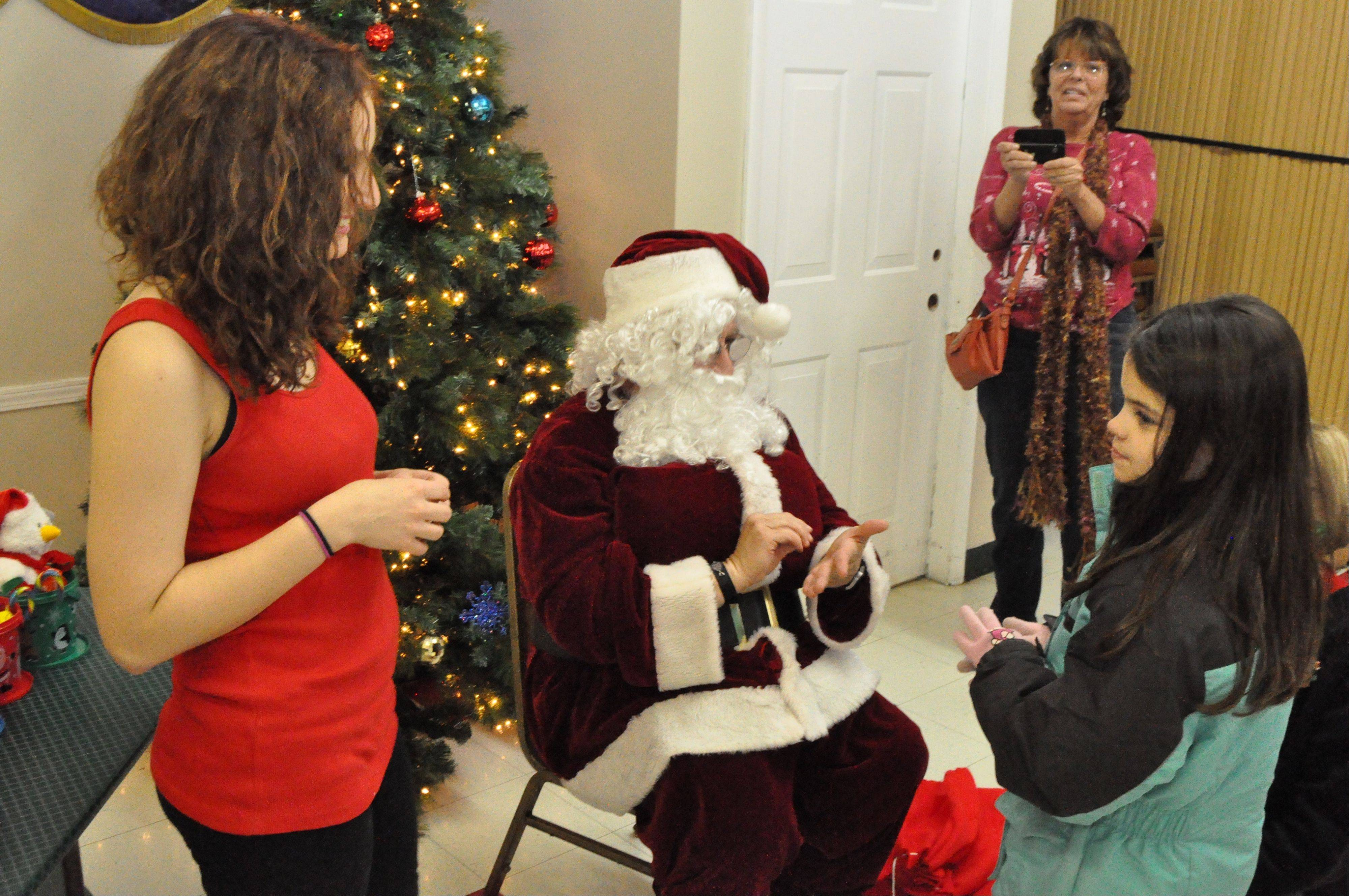 Santa brings joy and presents to 100 hearing-impaired kids at a recent pizza party. Helping him out are Angela Hatcher of Aurora, a West Aurora High School senior and Santa's assistant; and Jeanne McDonald, Naperville, a deaf teacher at Allen Elementary School, Aurora.