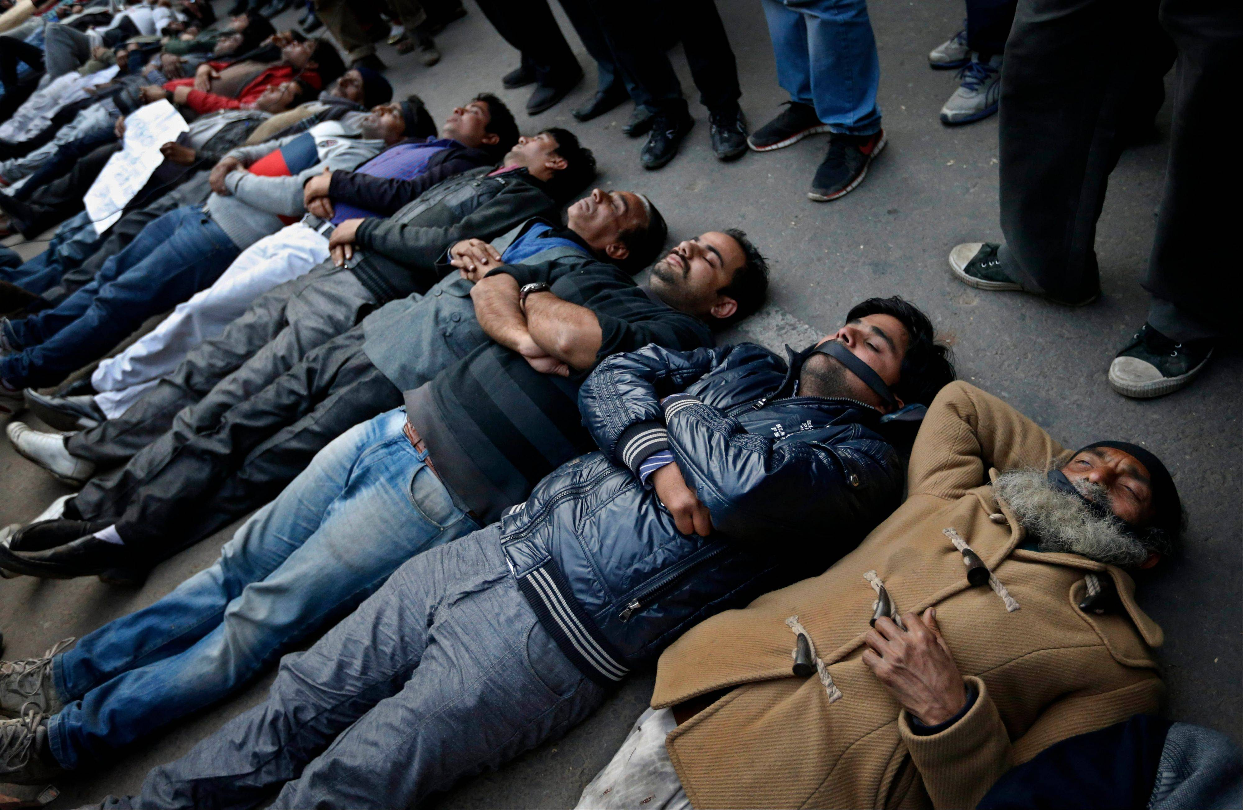 Indian men and women lie down on the ground Saturday mimicking dead bodies as they mourn the death of a gang rape victim in New Delhi, India.