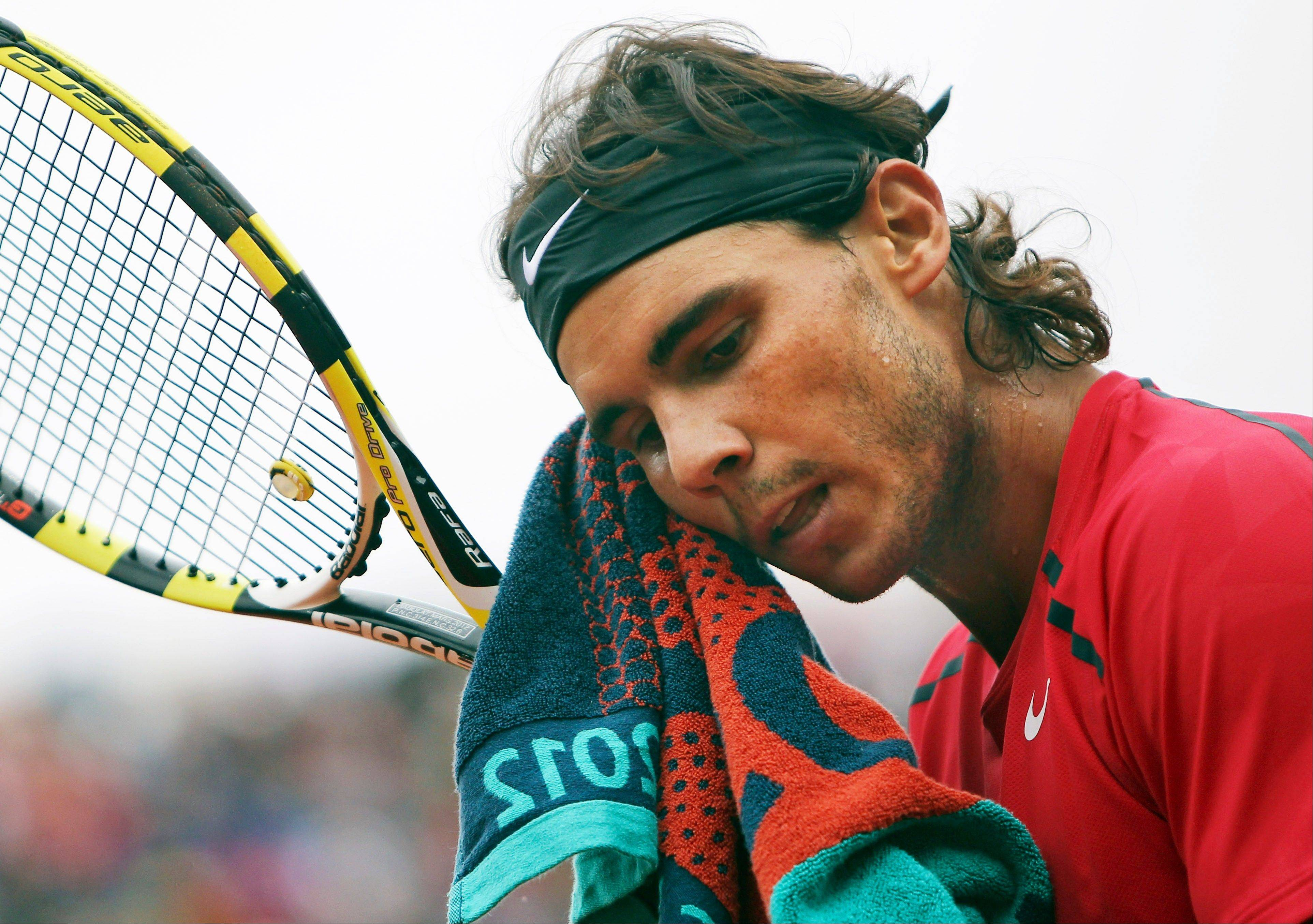 Spain�s Rafael Nadal wipes his face as he plays Serbia�s Novak Djokovic during their men�s final match in the French Open tennis tournament. Nadal will miss the Australian Open because of a stomach virus.