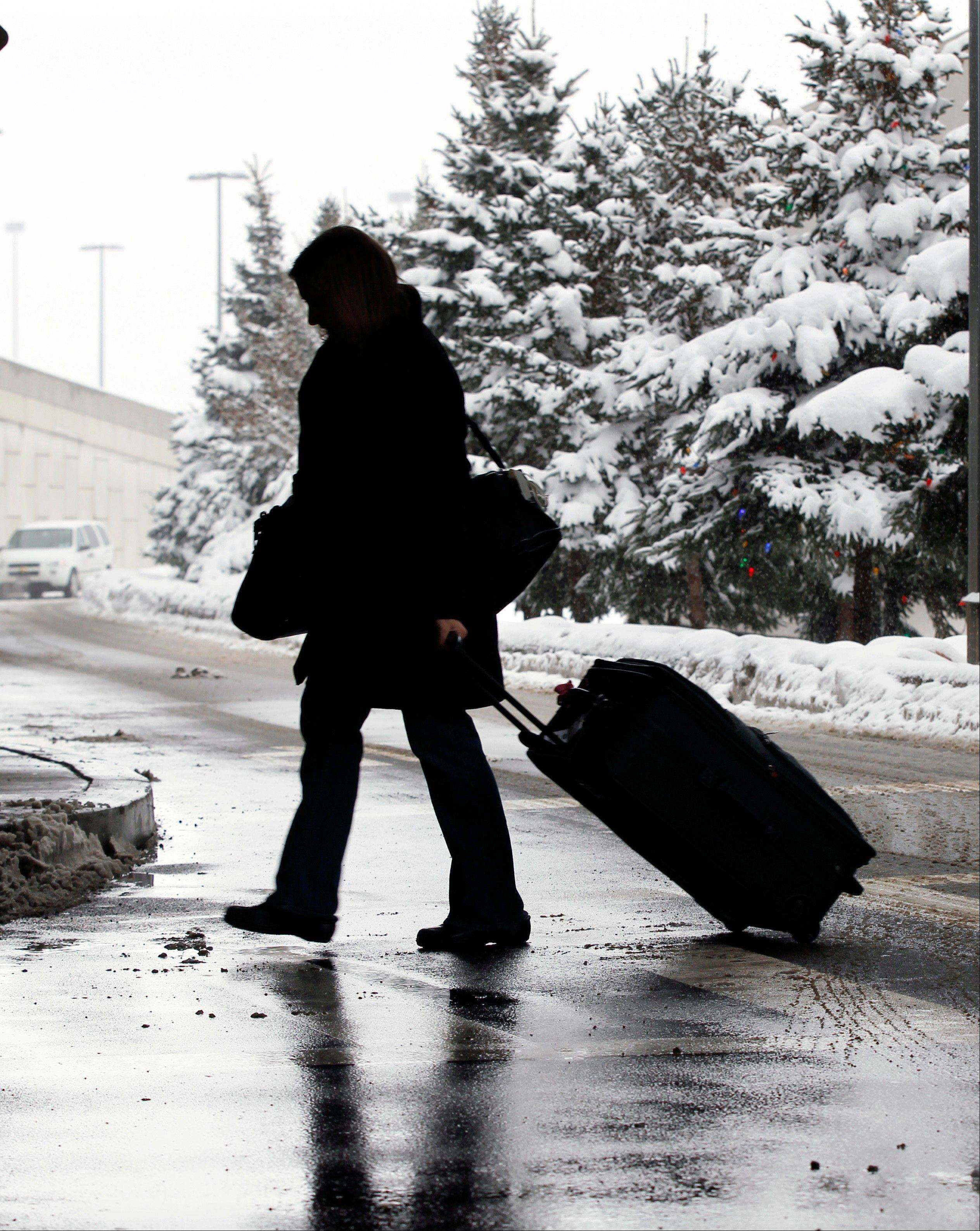 A person walks in a snowfall Saturday at Buffalo Niagara International Airport in Buffalo, N.Y.