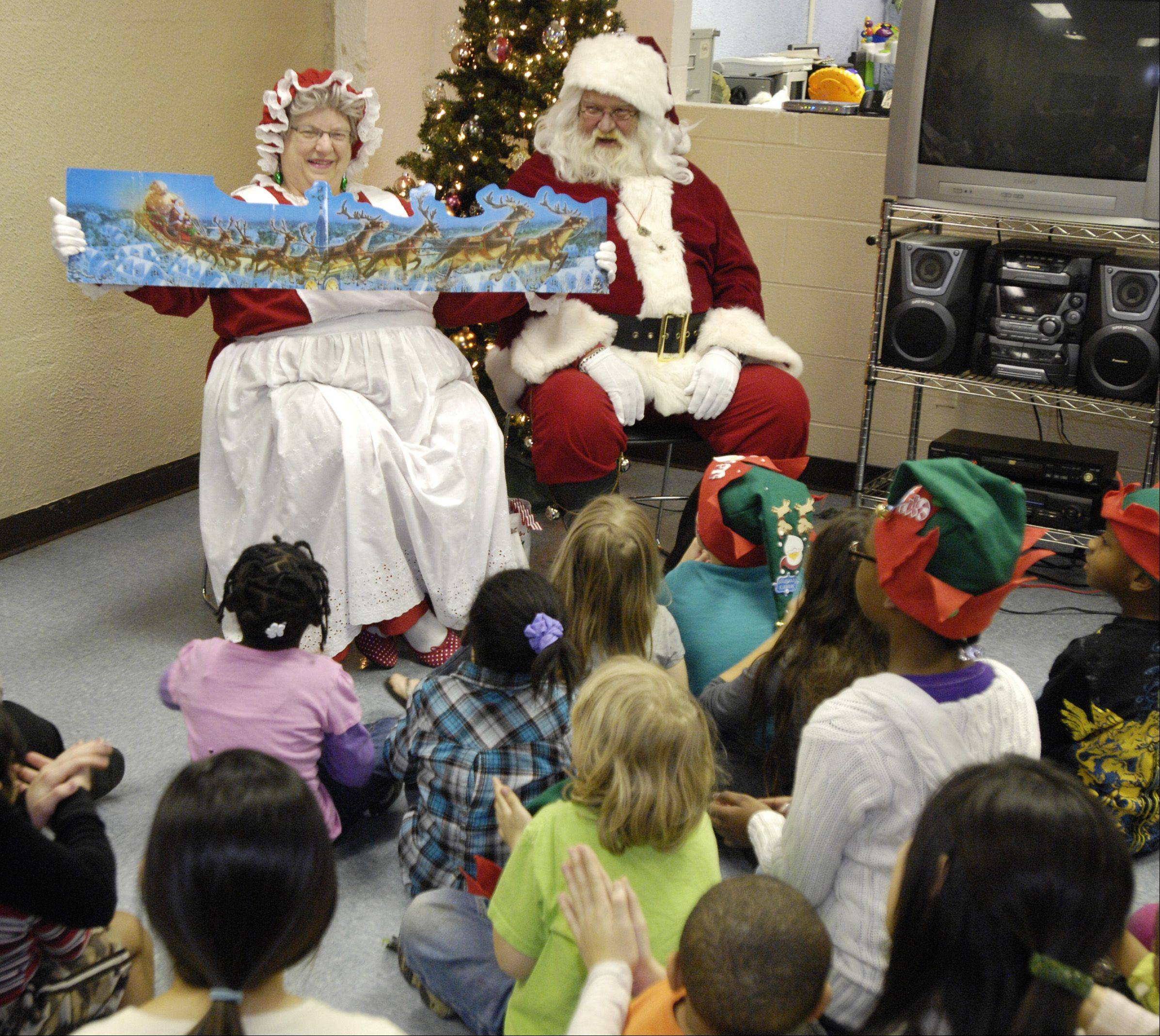 "Mrs. Claus reads ""'Twas the Night before Christmas"" to children at Hesed House in Aurora while Santa looks on. Also known as Ted and Marianne Wilkinson, the couple have been playing Santa and Mrs. Claus in the Aurora area for 24 years."