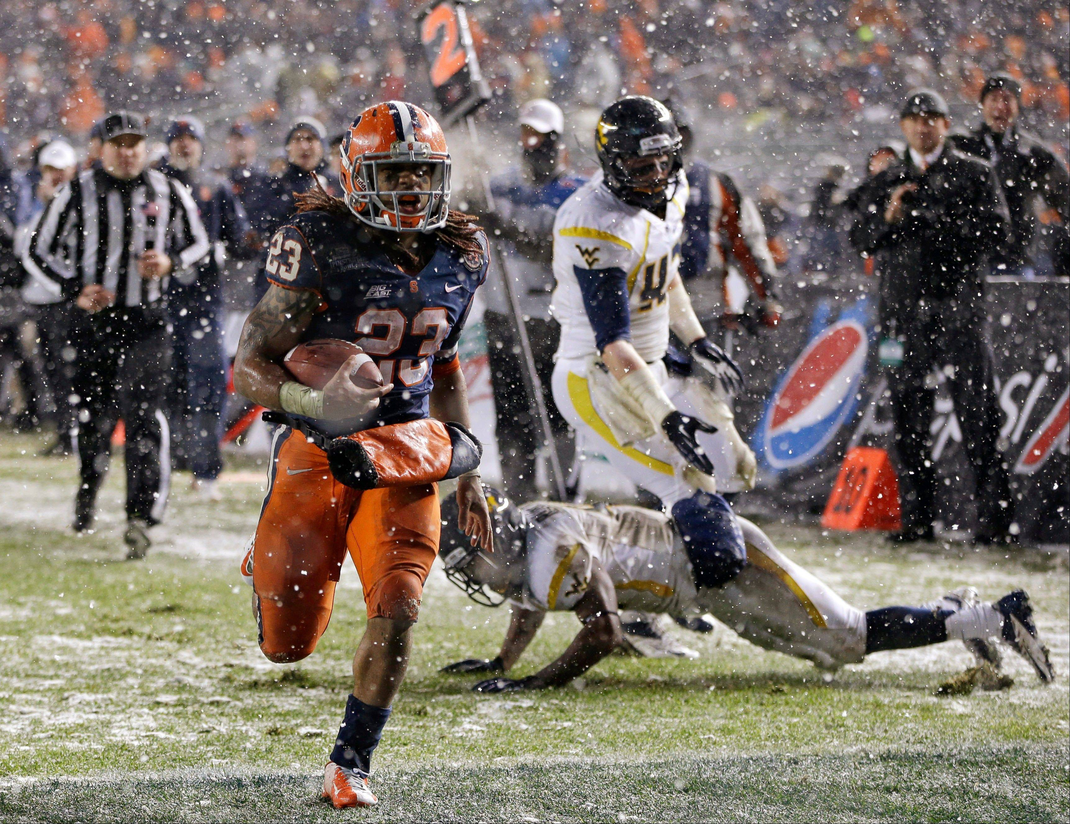 Syracuse running back Prince-Tyson Gulley (23) scores a touchdown, leaving West Virginia defenders in his wake during the third quarter of the Pinstripe Bowl NCAA college football game at Yankee Stadium in New York, Saturday, Dec. 29, 2012. Sryacuse won 38-14. (AP Photo/Kathy Willens)
