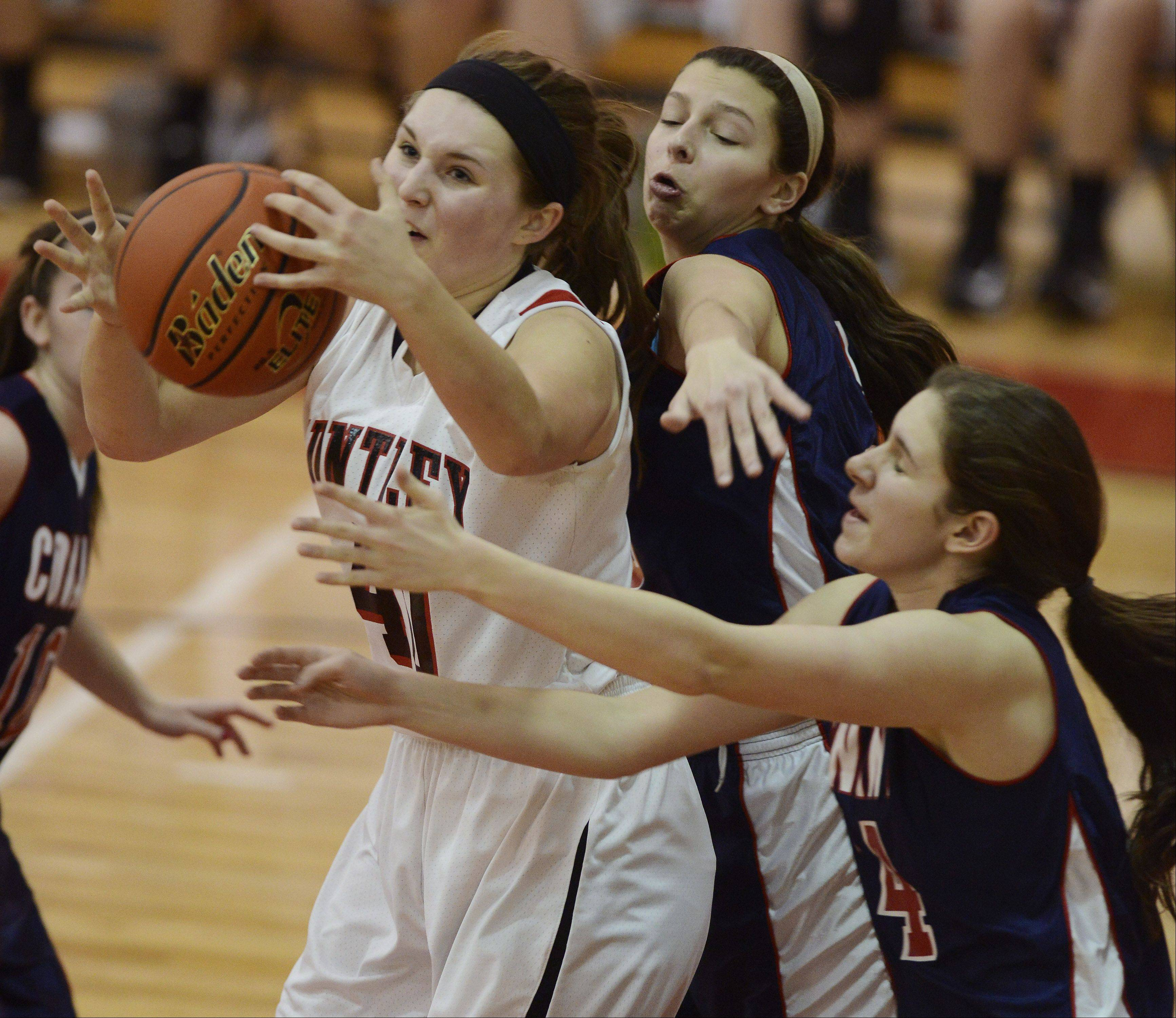 Huntley�s Sam Andrews, left, grabs a rebound in front of Conant�s Dee Dee Durr and Sarah Mazurek during Saturday�s game at Mundelein.