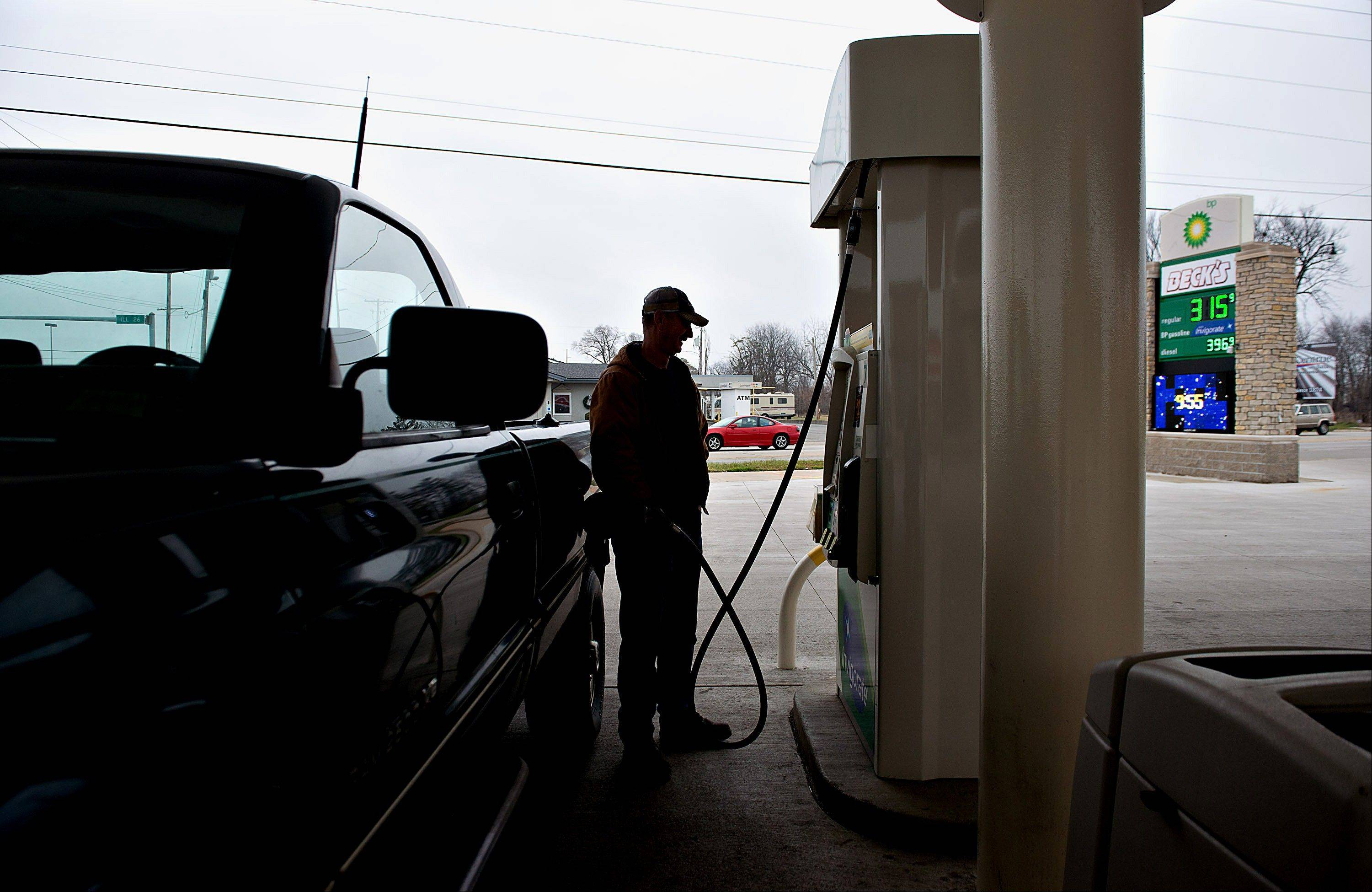 Gas prices are displayed, right, as a customer fills his truck with fuel Tuesday at a gas station in Princeton, Ill.