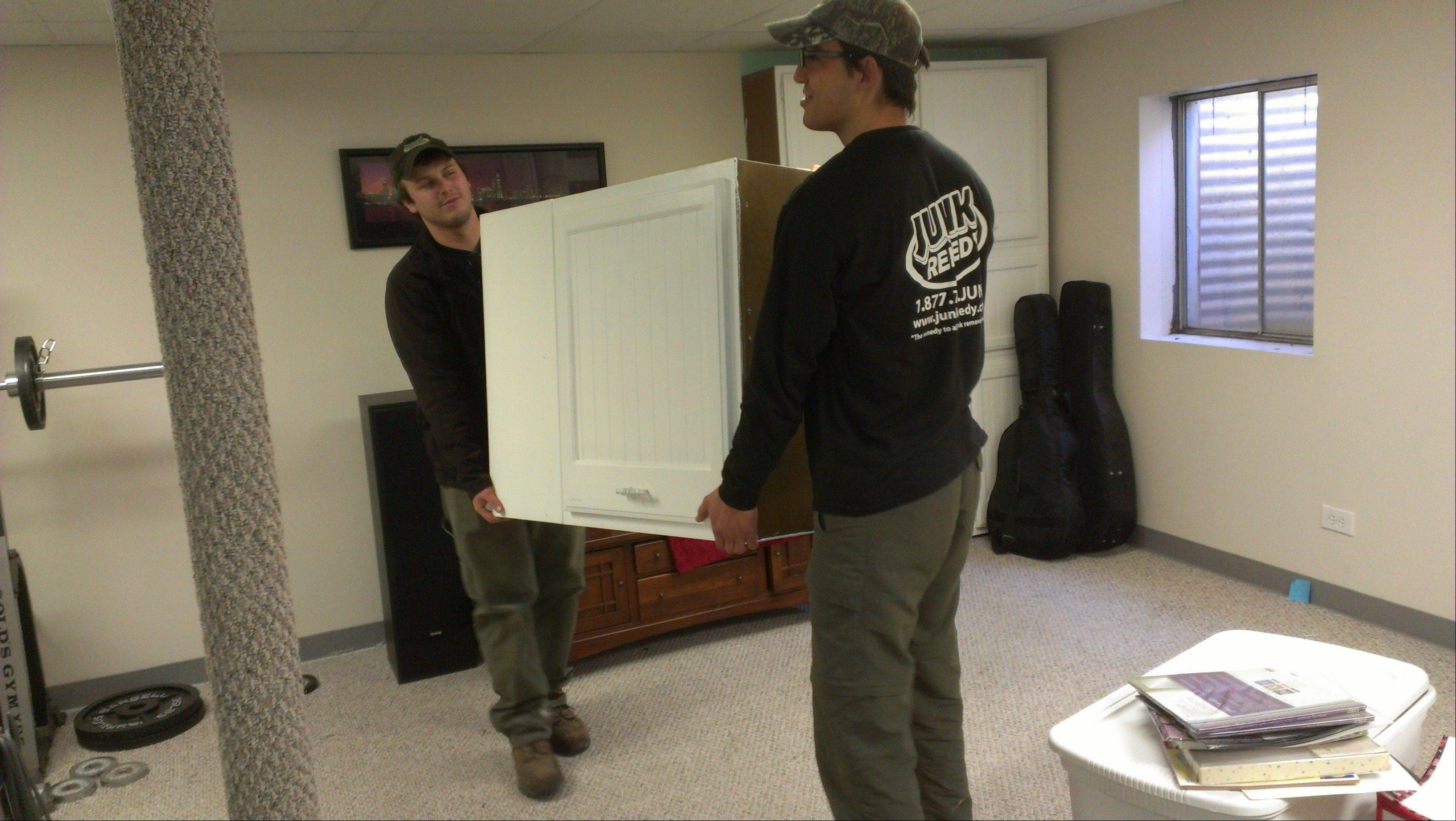 Zack Compton and Derek Moser of Junk Remedy in Lake Zurich remove a cabinet from a home remodeling job.