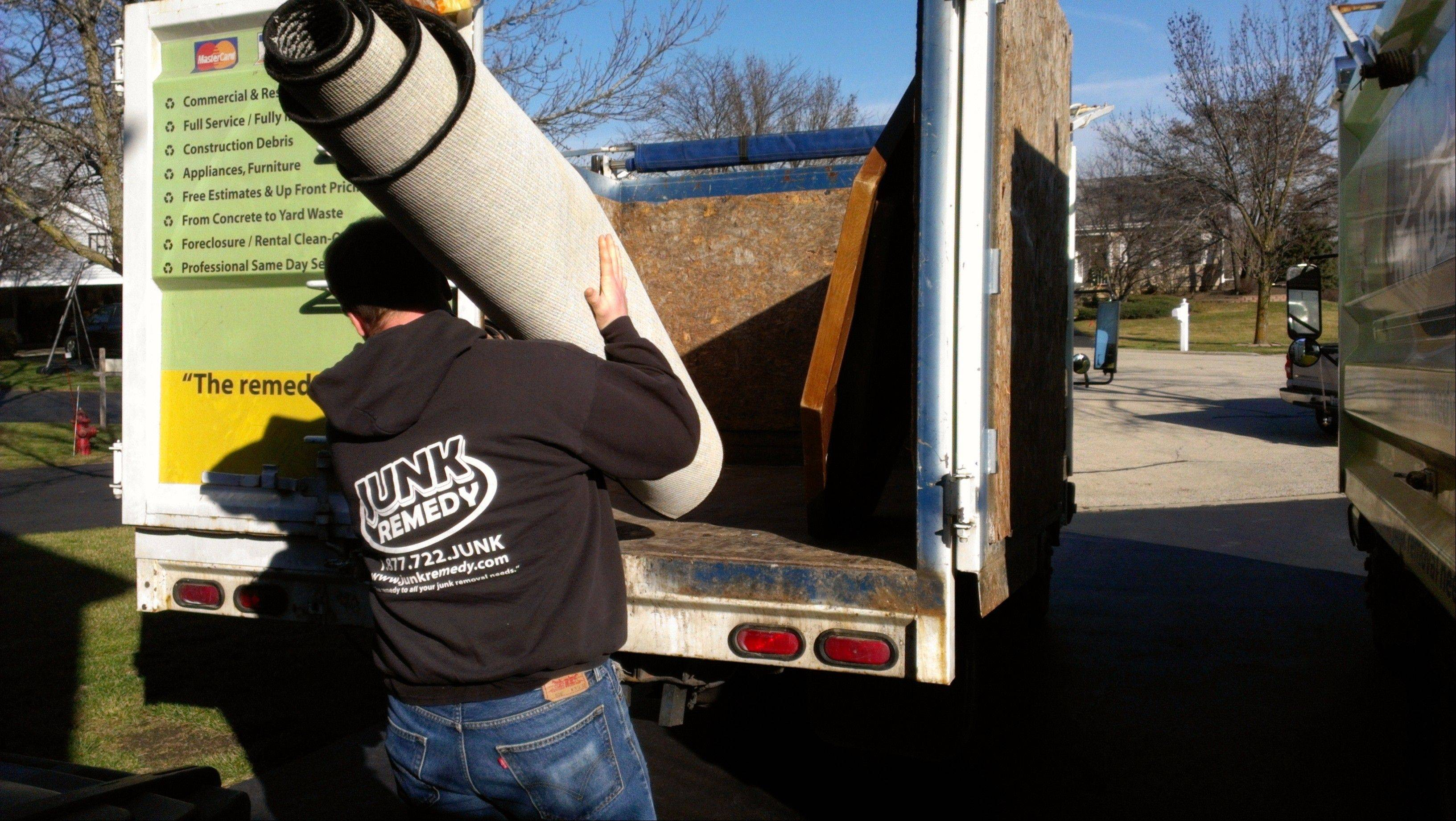 Junk Remedy employee Adam Brehmer hauls off an old carpet as part of a job removing debris.