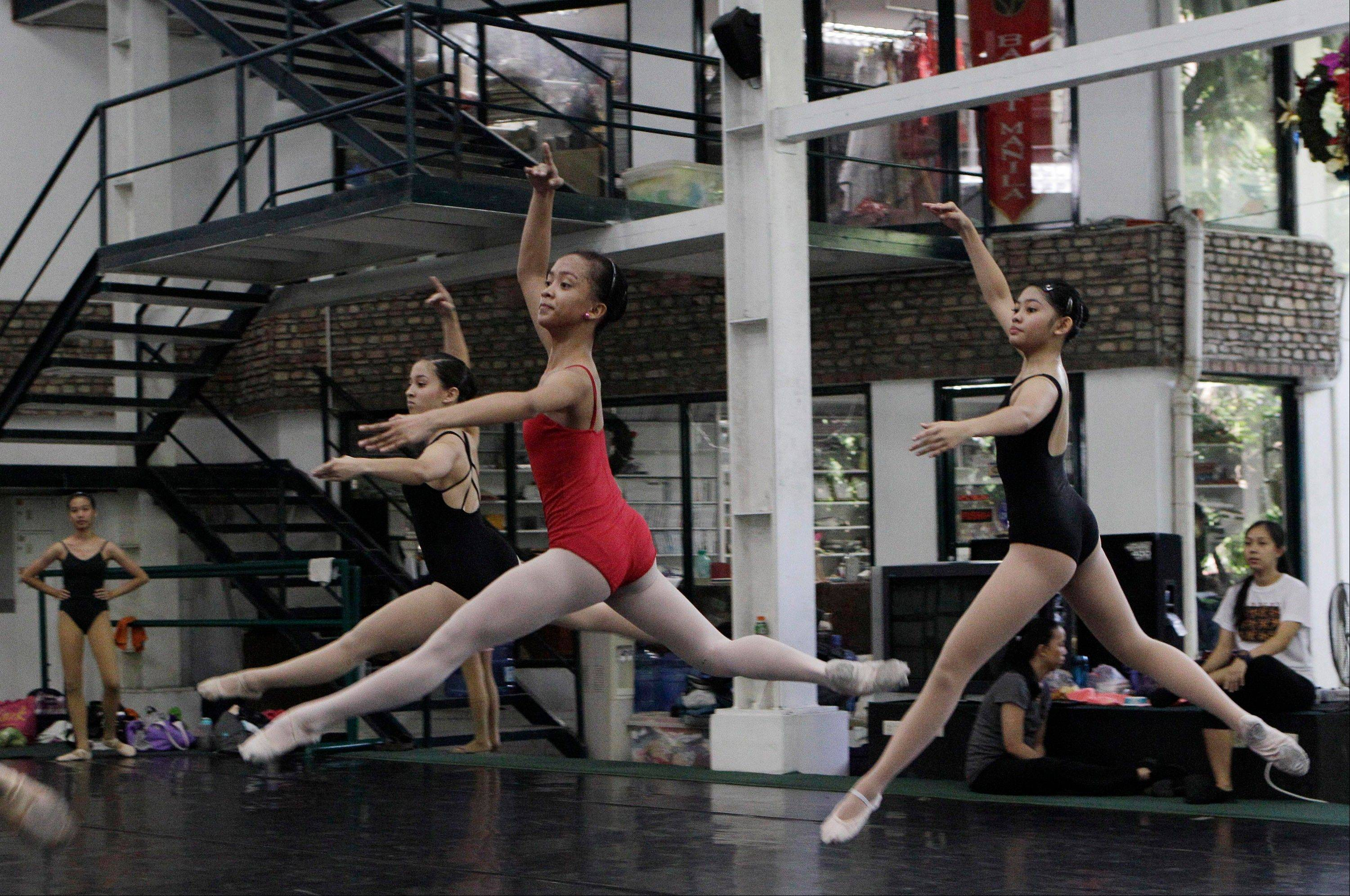 Filipino slum dweller Jessa Balote, center, practices with other students during a class at Ballet Manila in the Philippine capital. As an apprentice, she makes around $170 a month, sometimes double that, from stipend and performance fees.
