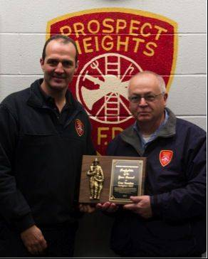 Firefighter Gus Tsoulos, left, gets a plaque from Fire Chief Donald R. Gould Jr.