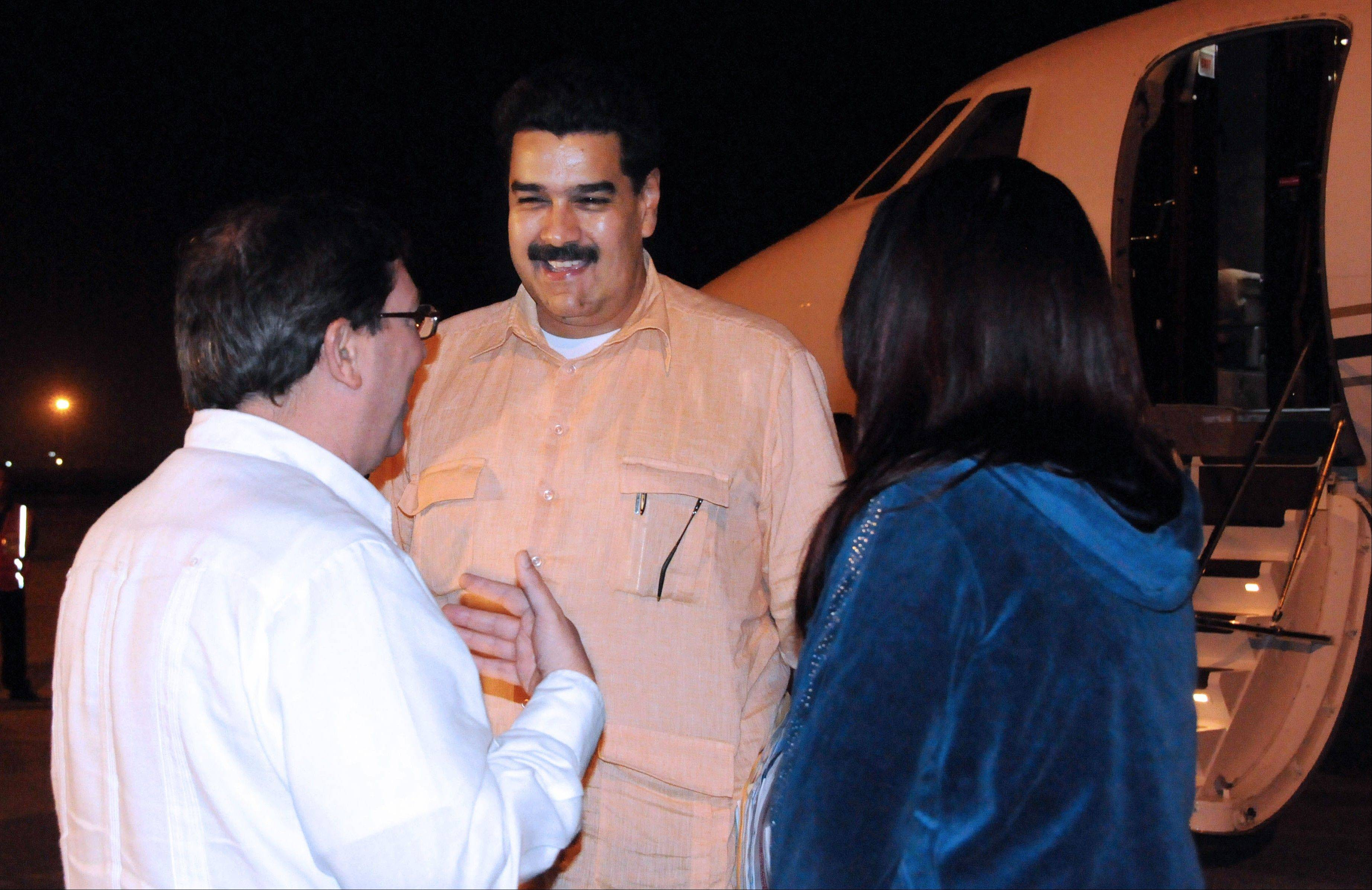 Cuban Foreign Minister Bruno Rodriguez , left, talks Saturday with Venezuela's Vice President Nicolas Maduro, center, as Venezuelan Attorney General Cilia Flores watches at the Jose Marti International Airport in Havana.