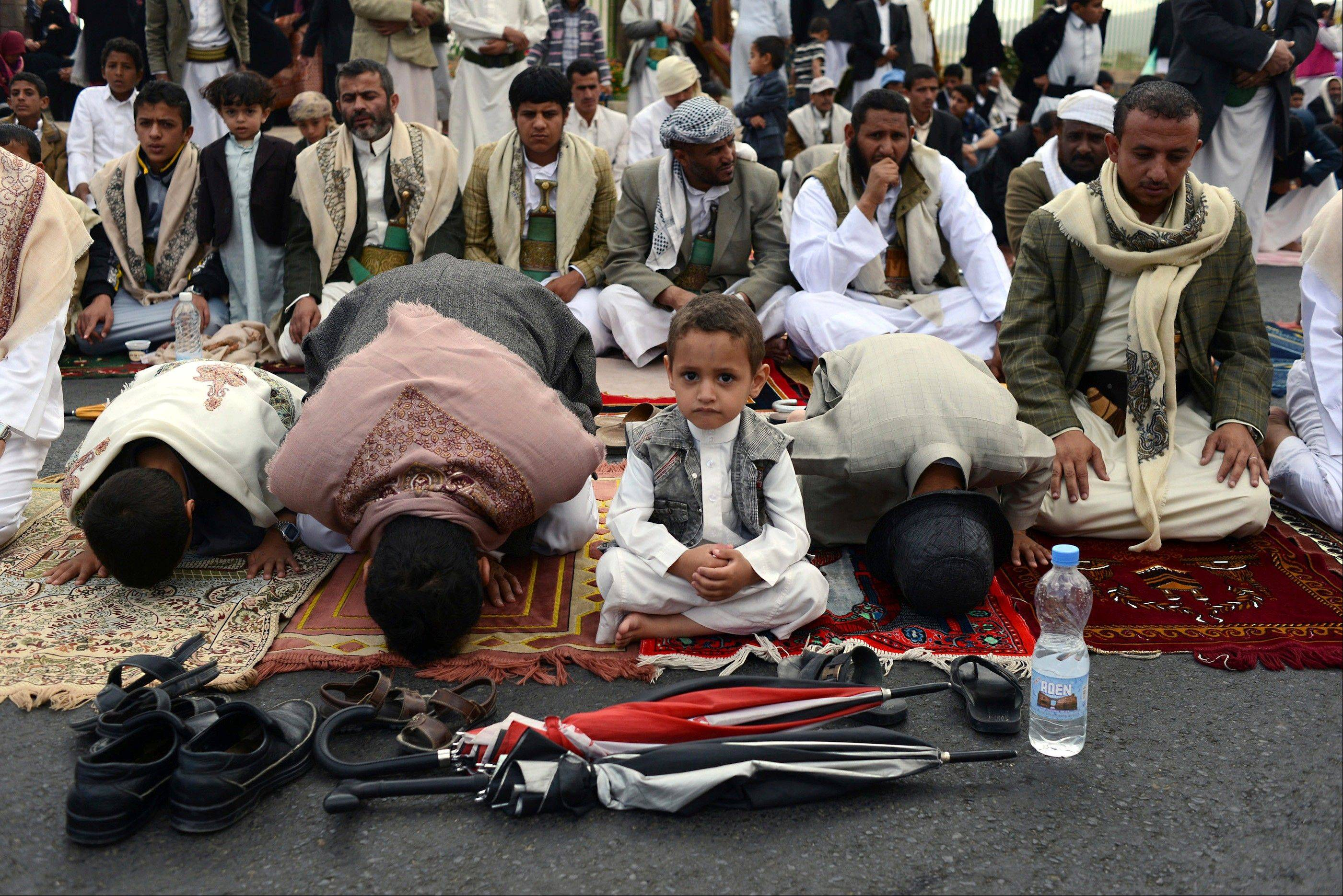 A Yemeni boy sits with his family while they pray Friday in Sanaa, Yemen. Since the beginning of the revolution, the Friday prayer has been held on 60 Street near Sanaa University, drawing thousands of people.