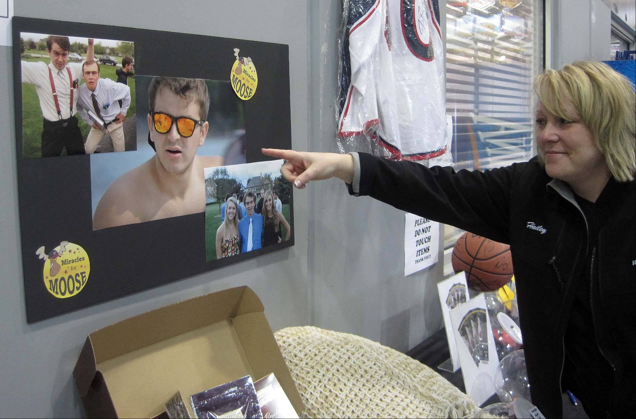 "Hailey Kenny, one of five Crystal Lake moms who spearheaded the Miracles for Moose Foundation, points to photos of 18-year-old Anthony ""Moose"" Mustari, of Crystal Lake, who is battling a rare form of leukemia. A benefit hockey game was held Saturday at Leafs Ice Centre in West Dundee to raise funds for the Mustari family."
