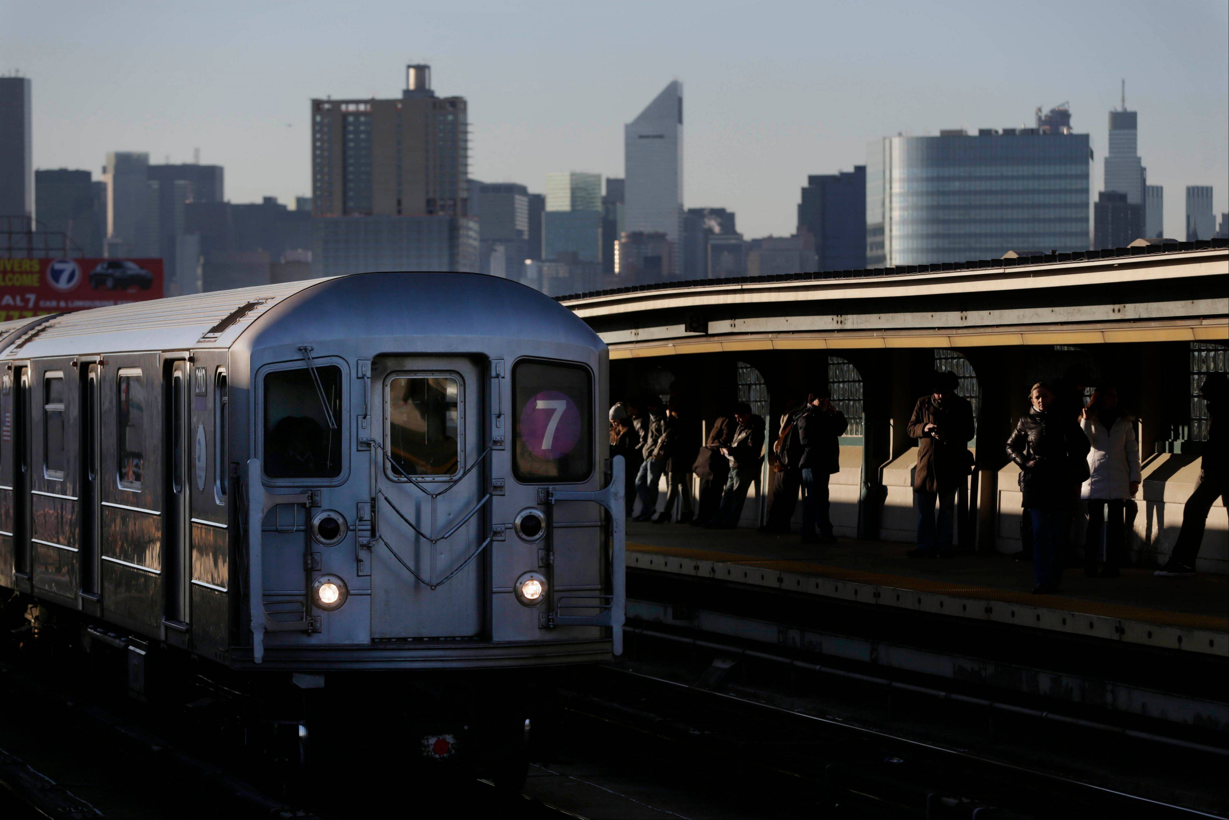 Commuters wait on the platform Friday as a train passes through the 40th St-Lowry St Station, where a man was killed after being pushed onto the subway tracks, in the Queens section of New York.